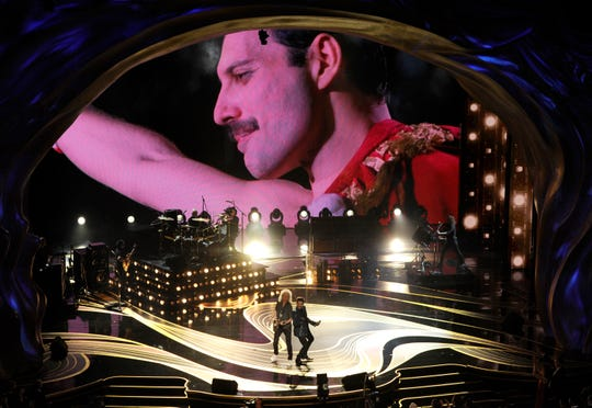 An image of Freddie Mercury appears on screen as Brian May, left, and Adam Lambert of Queen perform at the Oscars on Sunday.