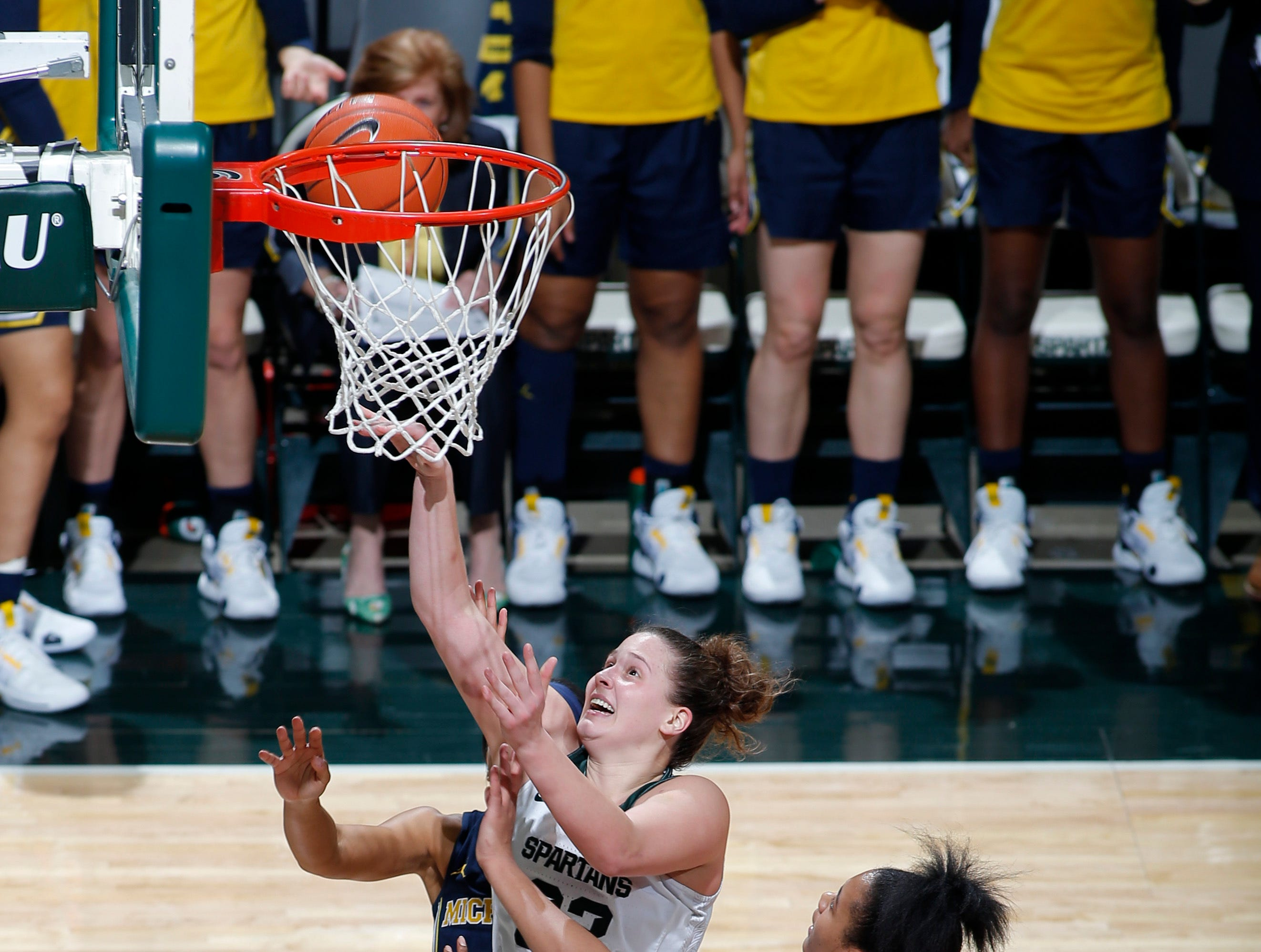 Michigan State's Jenna Allen, center, shoots against Michigan's Naz Hillmon (00) during the second quarter.