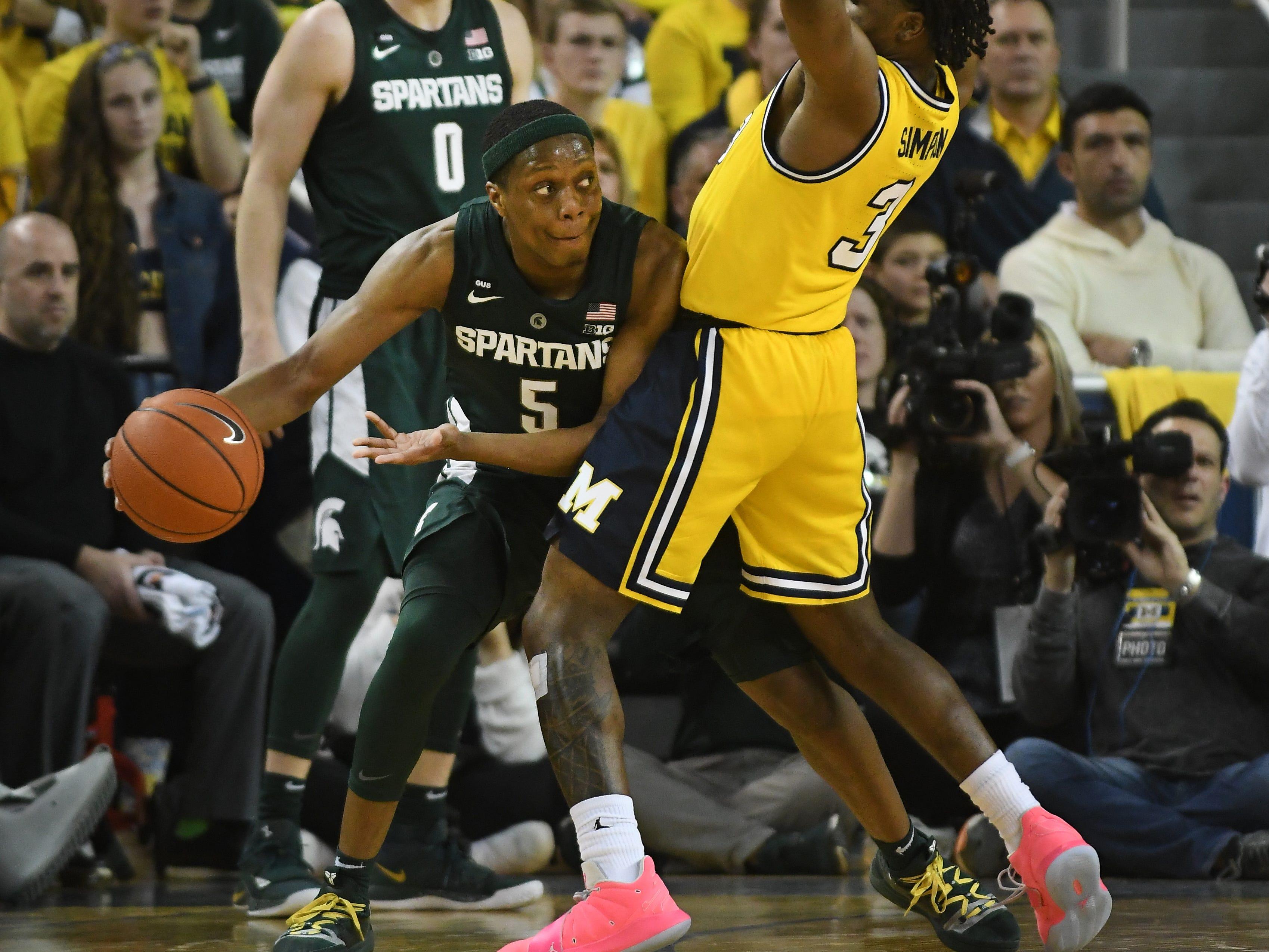 Michigan State's Cassius Winston works around Michigan's Zavier Simpson in the second half.
