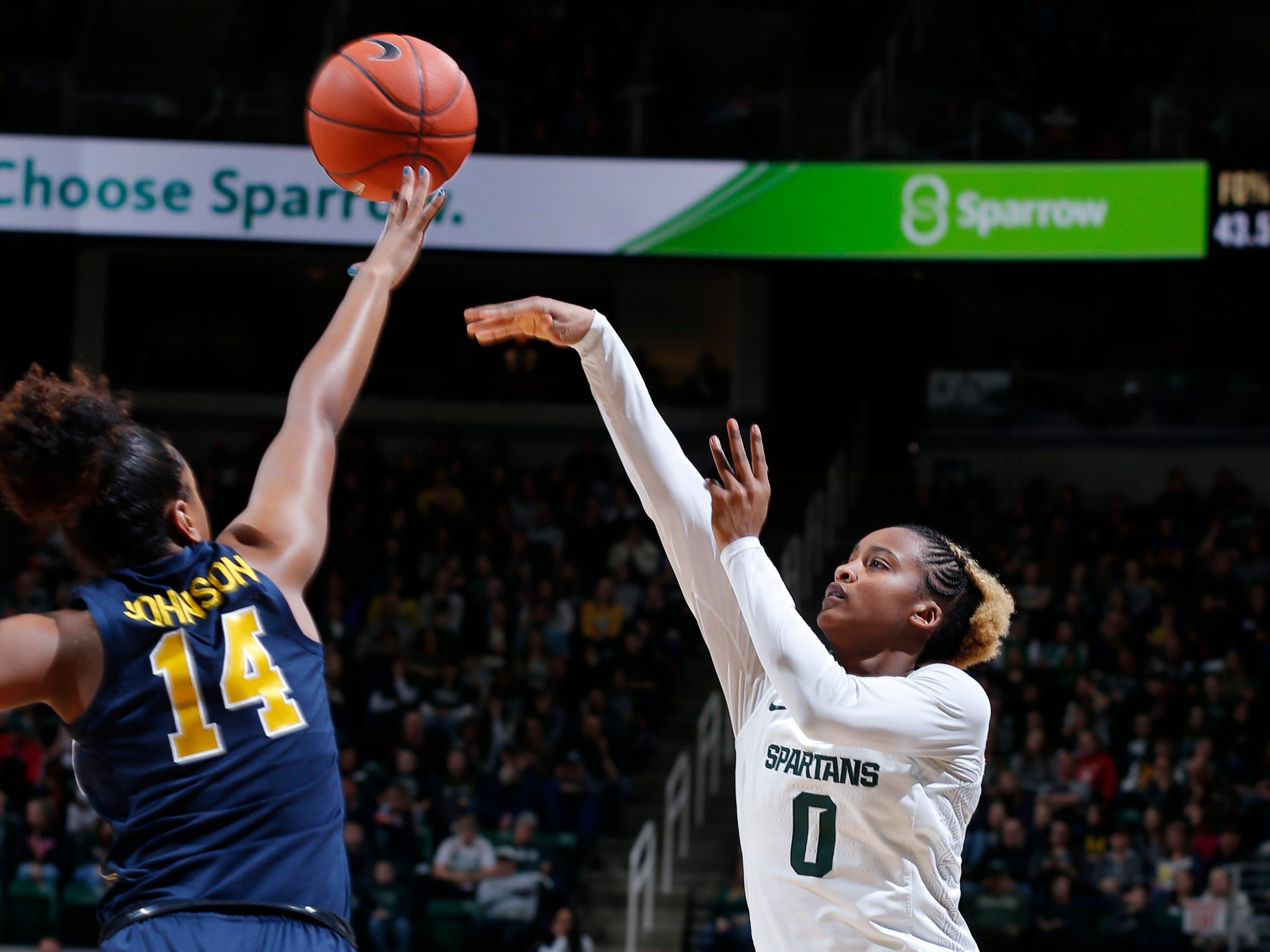 Michigan State's Shay Colley, right, shoots against Michigan's Akienreh Johnson (14).
