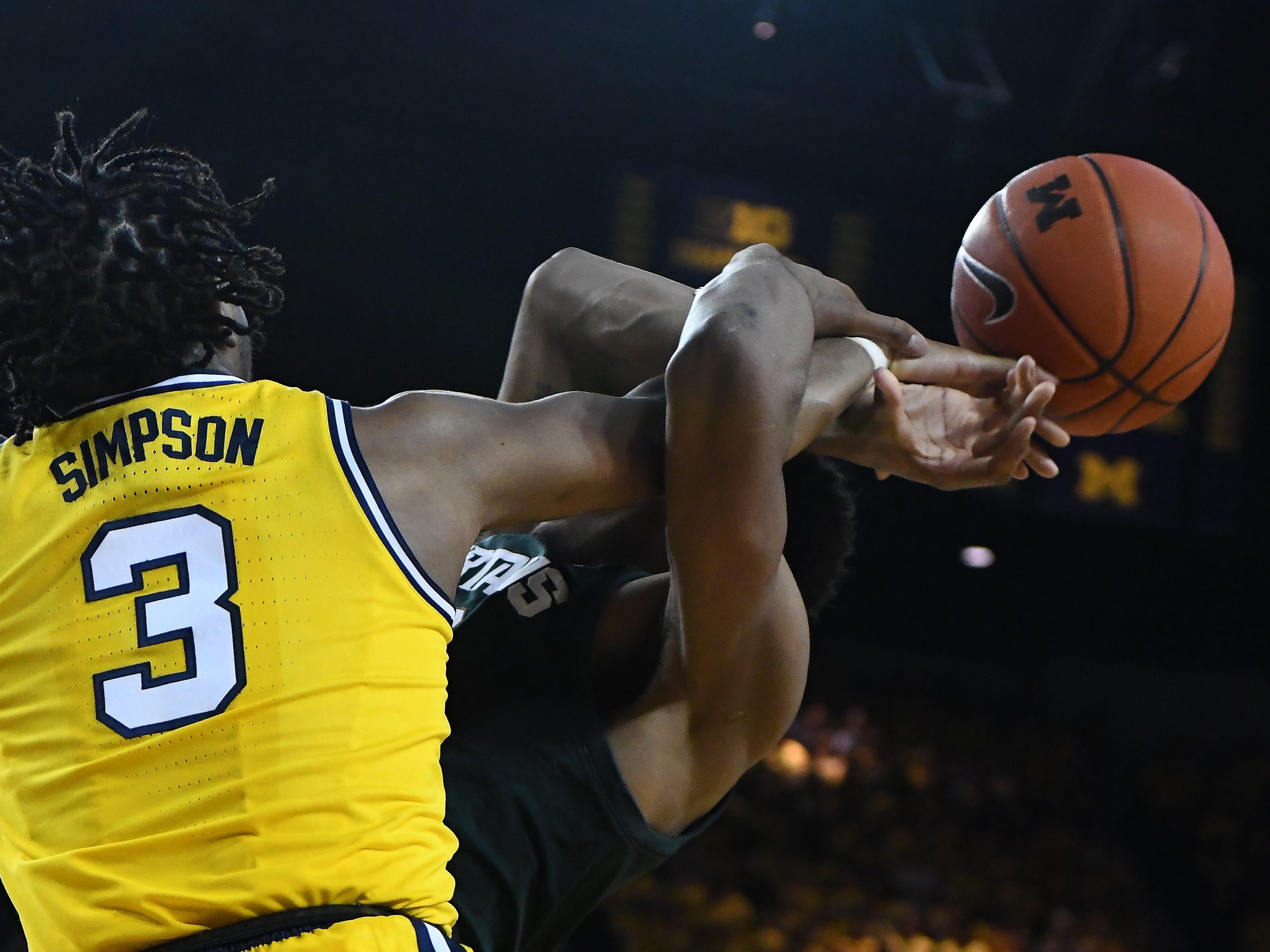 Michigan's Zavier Simpson blocks a shot by Michigan State's Zavier Tillman in the first half.