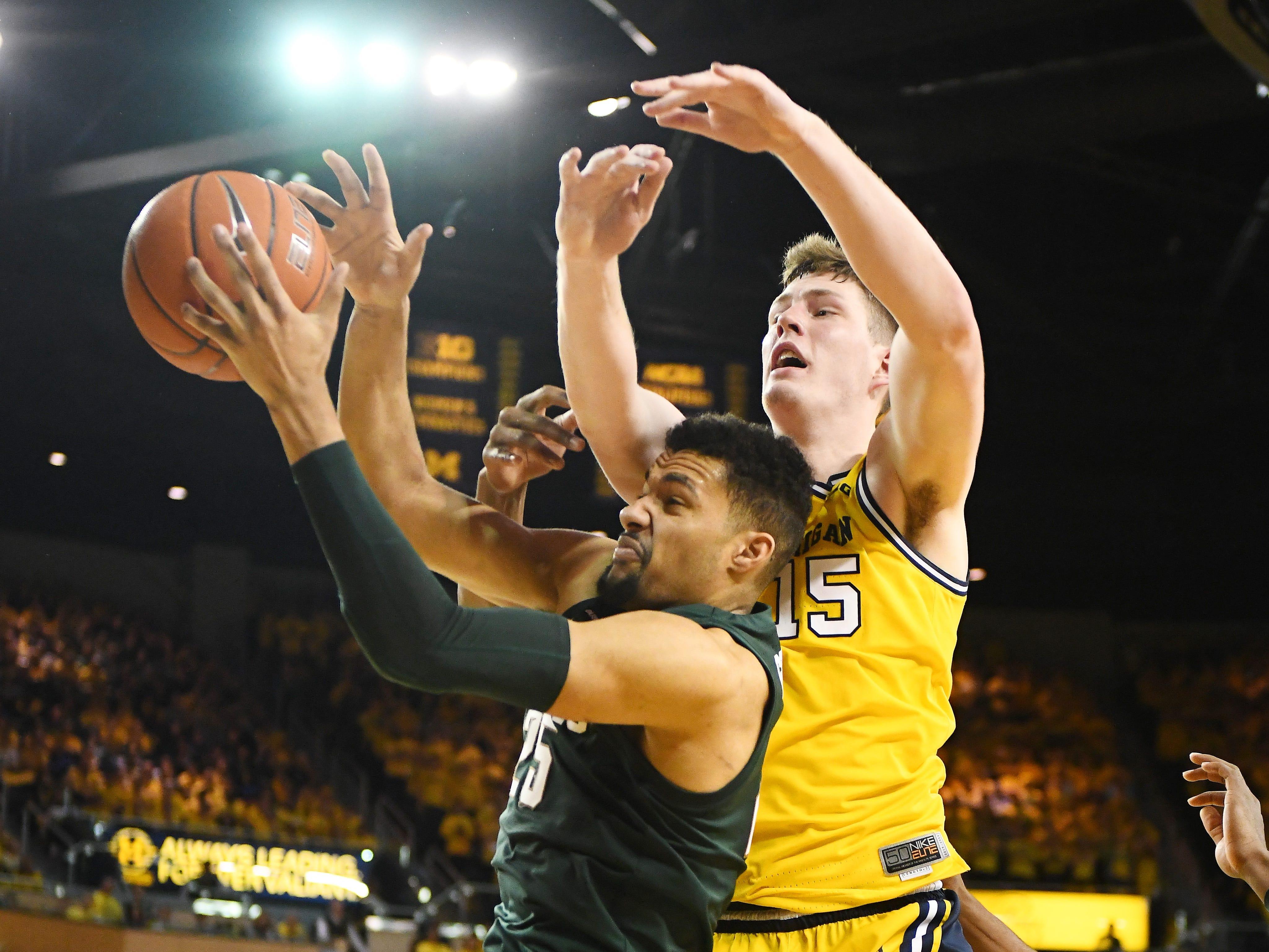 Michigan State's Kenny Goins pulls down a rebound under Michigan's Jon Teske in the second half.