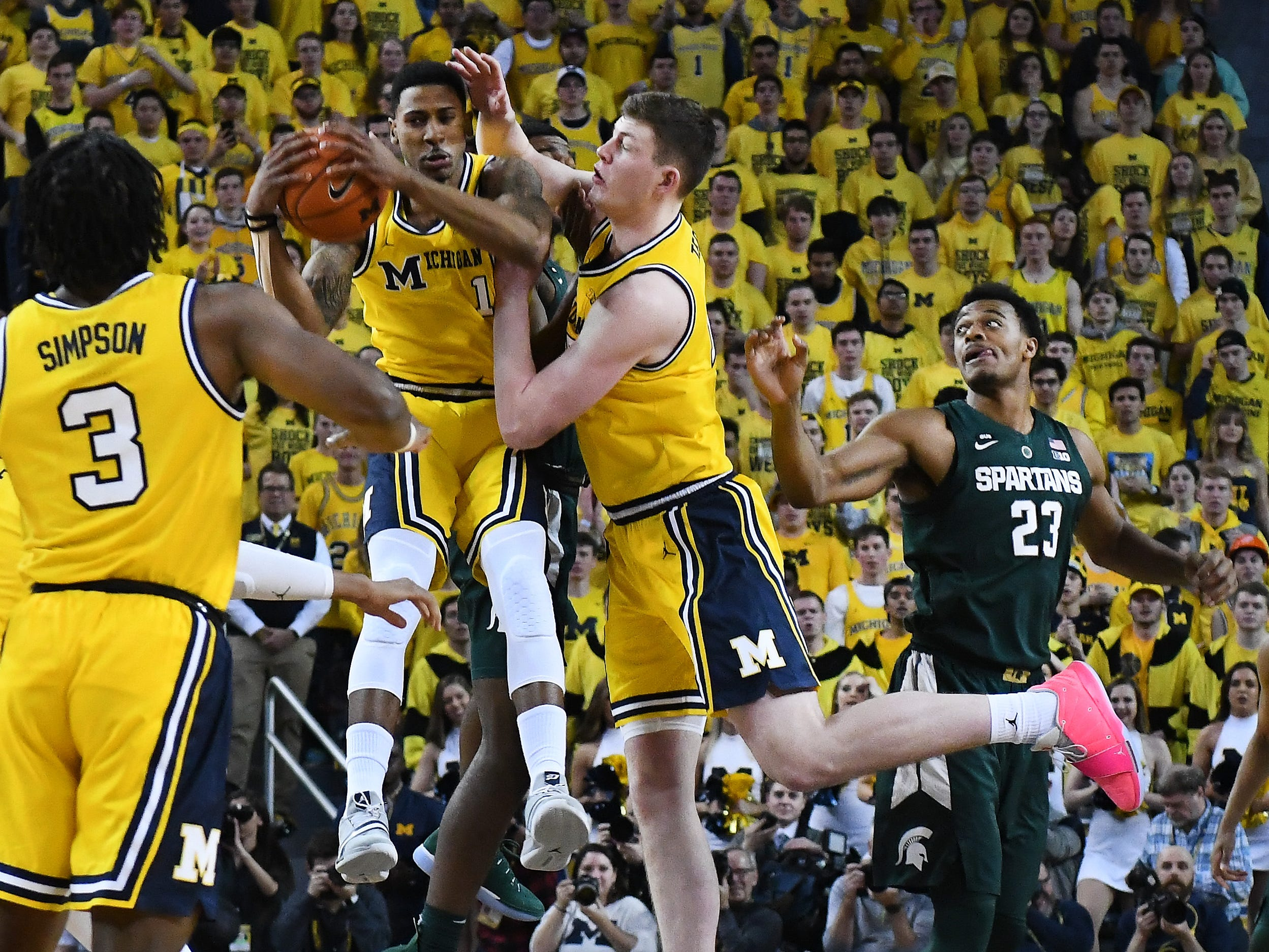 Michigan's Charles Matthews and Jon Teske collide going to the tip off ball at the start of the game.