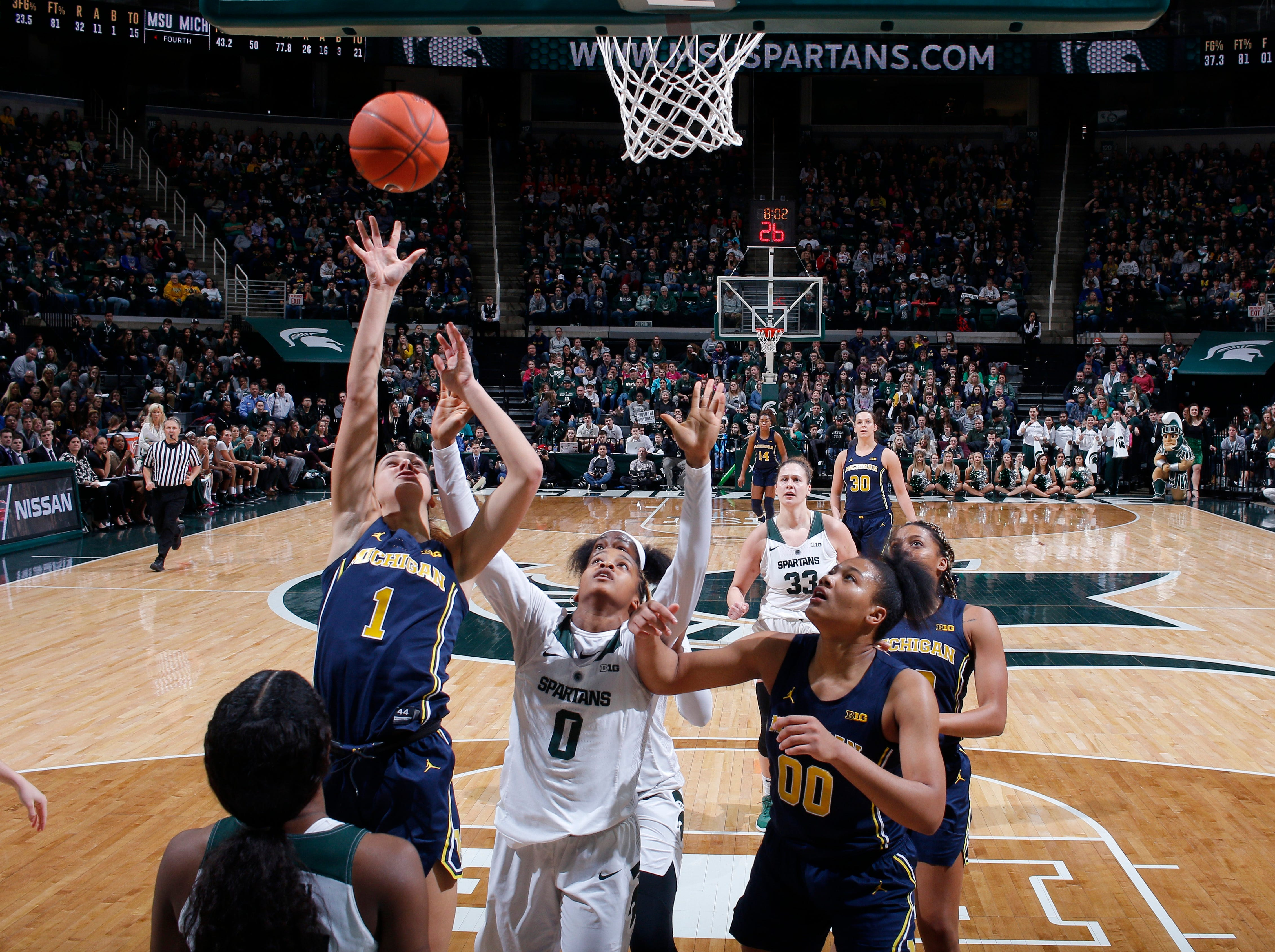 Michigan's Amy Dilk (1) shoots against Michigan State's Shay Colley (0) as Michigan's Naz Hillmon (00) watches during an NCAA college basketball game, Sunday, Feb. 24, 2019, in East Lansing, Mich. Michigan State won 74-64. (AP Photo/Al Goldis)