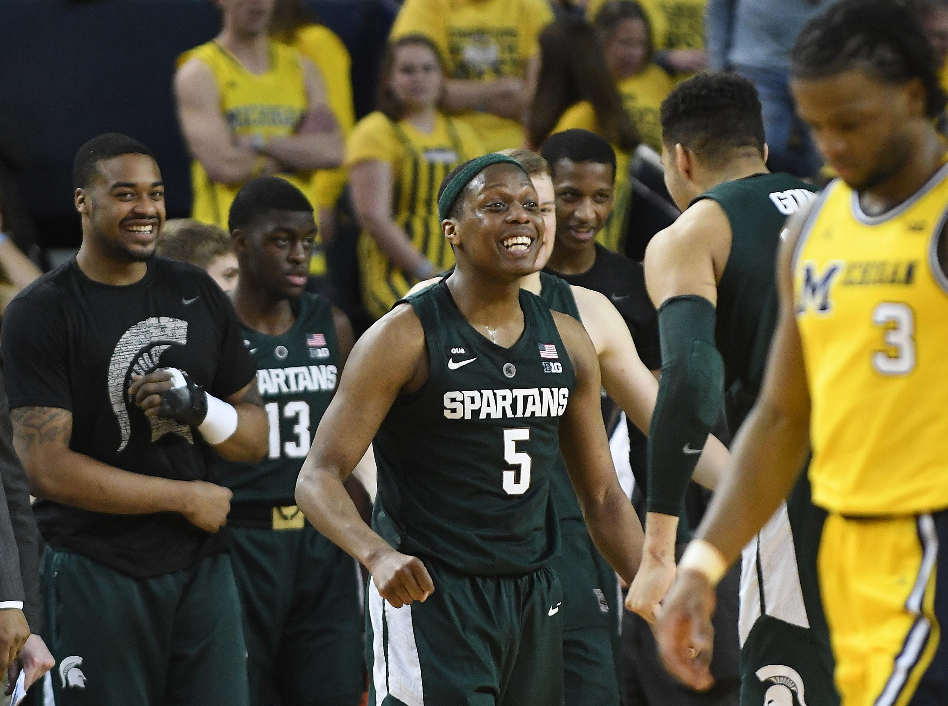 Michigan State's Cassius Winston celebrates as Michigan's Zavier Simpson walks off the floor after the State victory in the second half. University of Michigan vs. Michigan State at Crisler Center in Ann Arbor, Michigan on February 24, 2019.  (Image by Daniel Mears / The Detroit News)  77-70