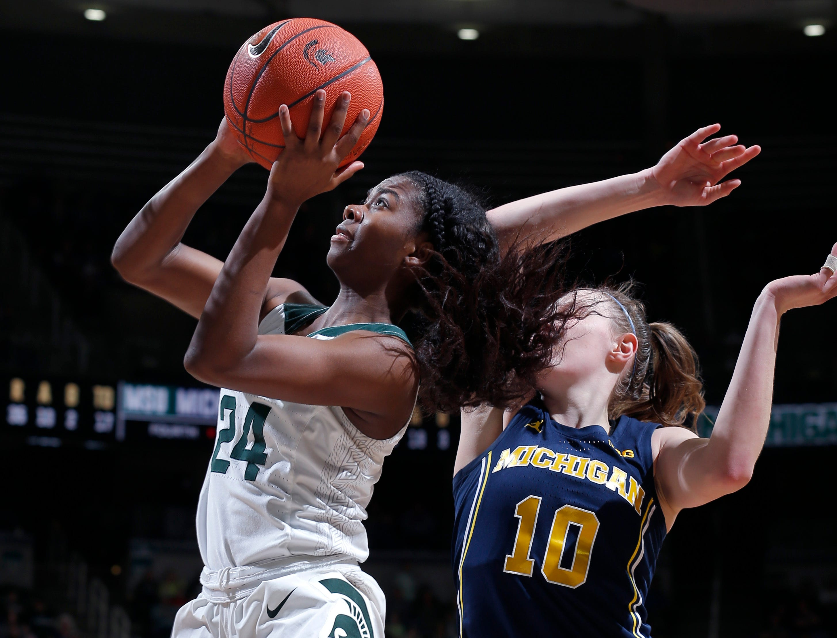 Michigan State's Nia Clouden, left, goes up for a layup against Michigan's Nicole Munger (10) during the fourth quarter.