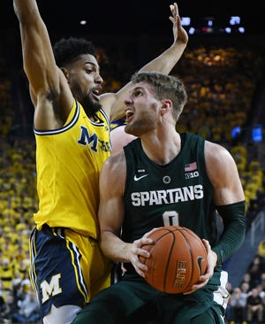 Michigan's David DeJulius and Michigan State's Kyle Ahrens go one-on-one near the basket in the first half.