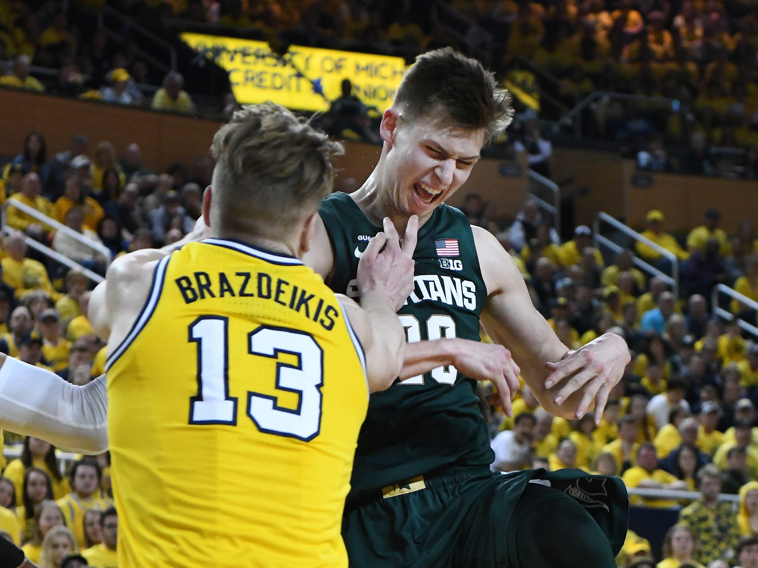Michigan's Ignas Brazdeikis defend against Michigan State's Matt McQuaid in the first half.