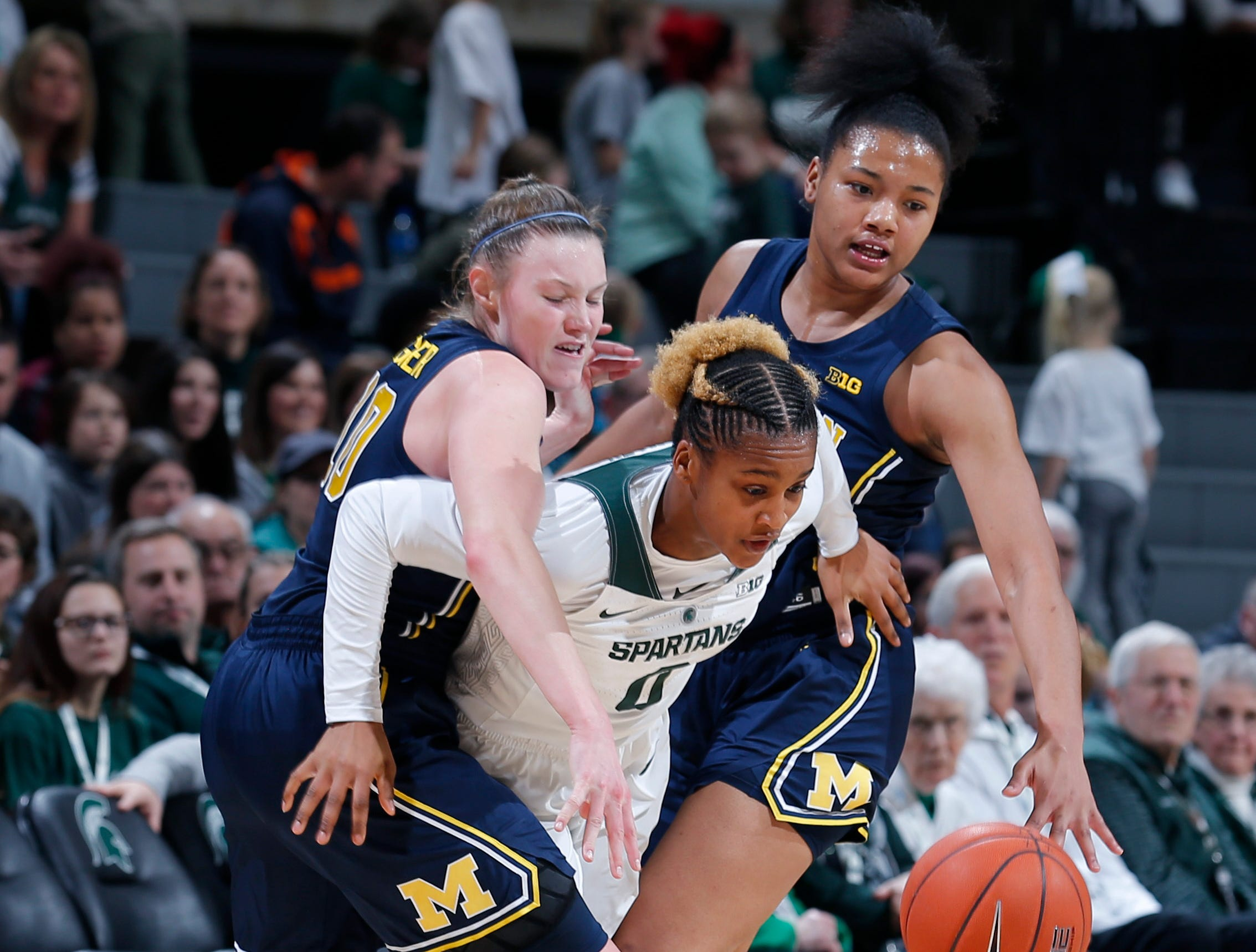 Michigan State's Shay Colley, center, escapes pressure by Michigan's Nicole Munger, left, and Naz Hillmon during the fourth quarter.