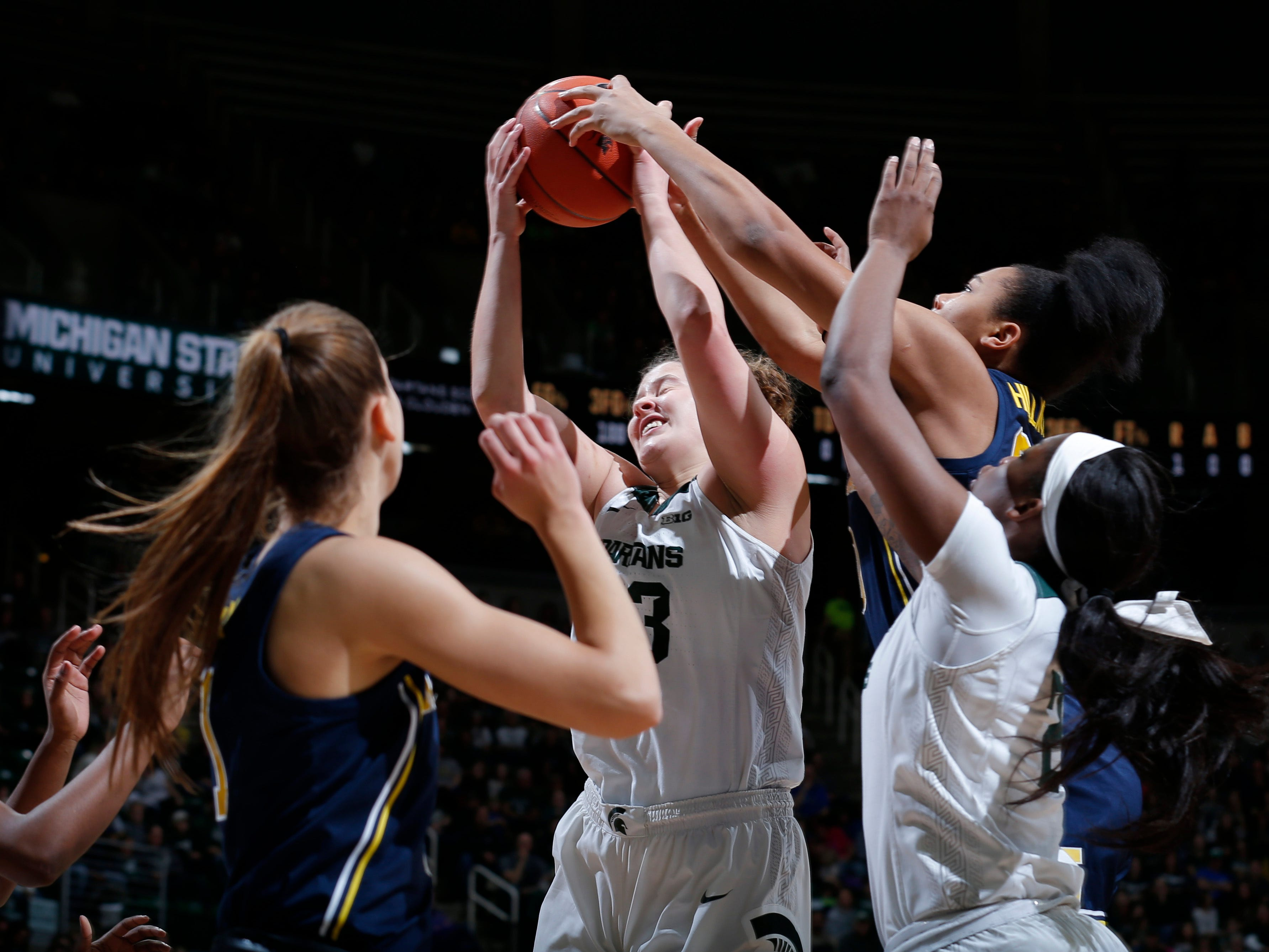 Michigan State's Jenna Allen, center, and Mardrekia Cook, right, and Michigan's Amy Dilk, left, and Naz Hillmon, top right, battle for a rebound.
