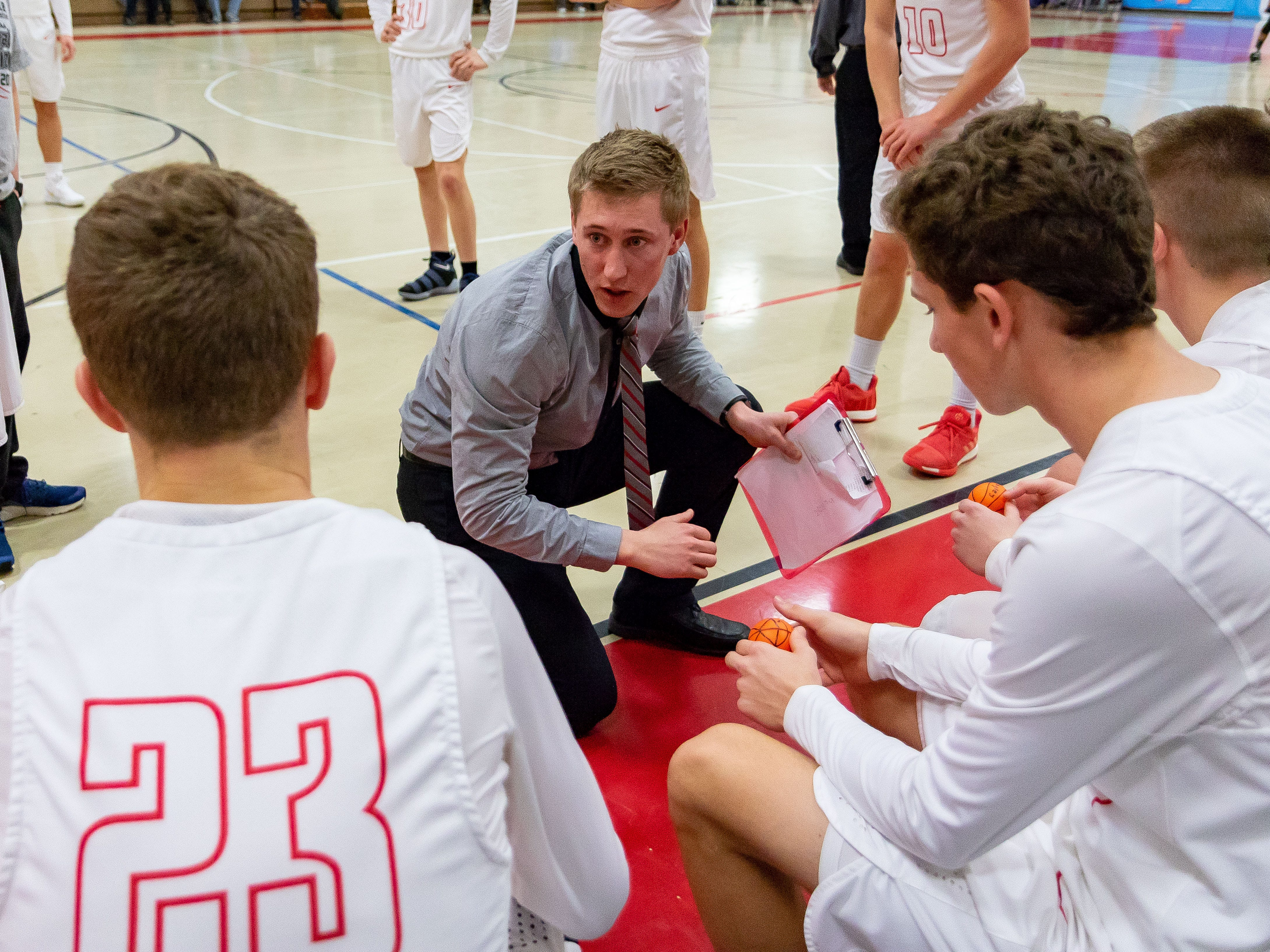 Justin Jergens, assistant varsity coach and brother of Dylan Jergens, provides some pregame instructions.