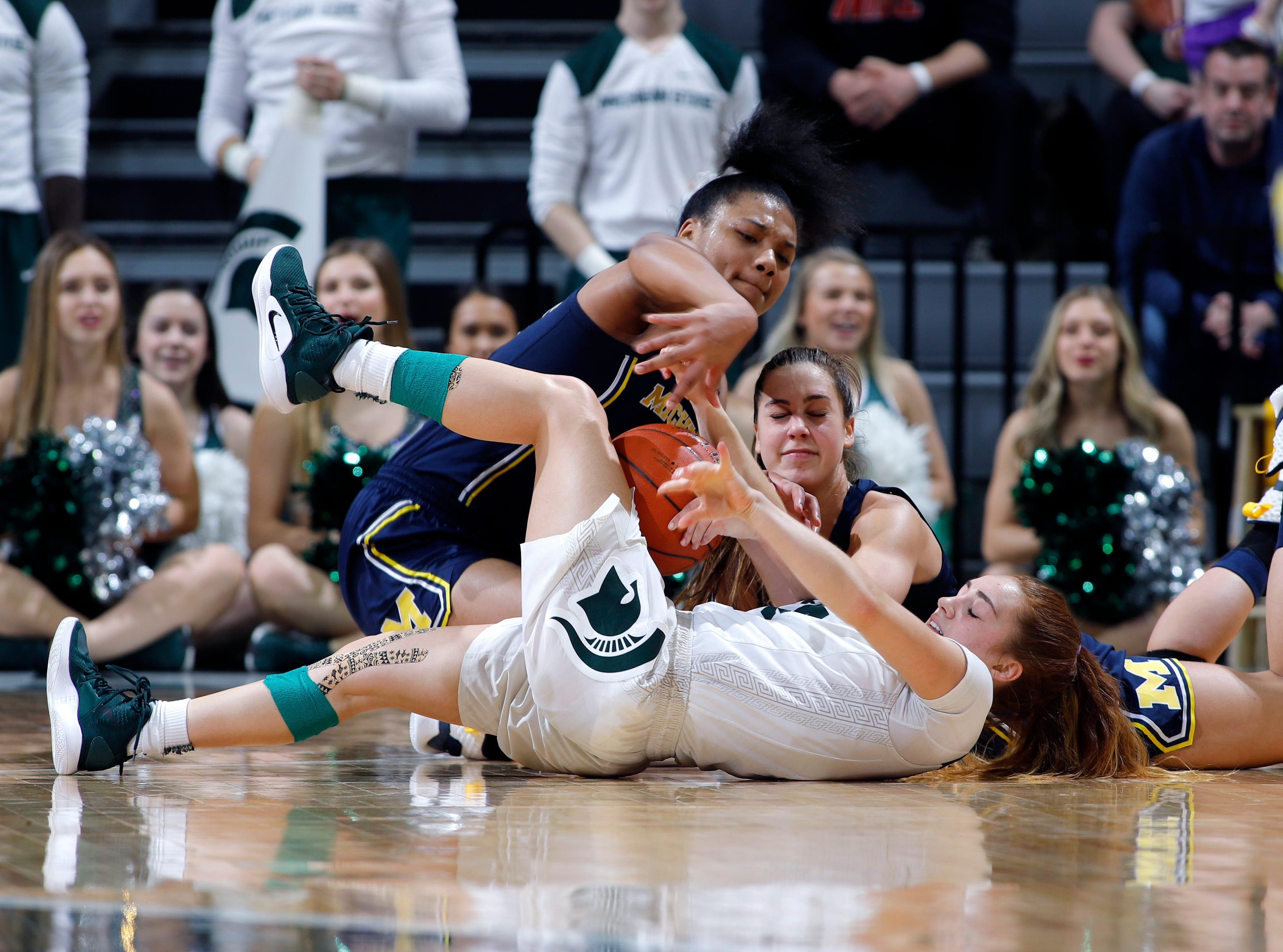 Michigan State's Taryn McCutcheon, bottom, and Michigan's Naz Hillmon, left, and Amy Dilk battle for the ball during the fourth quarter.