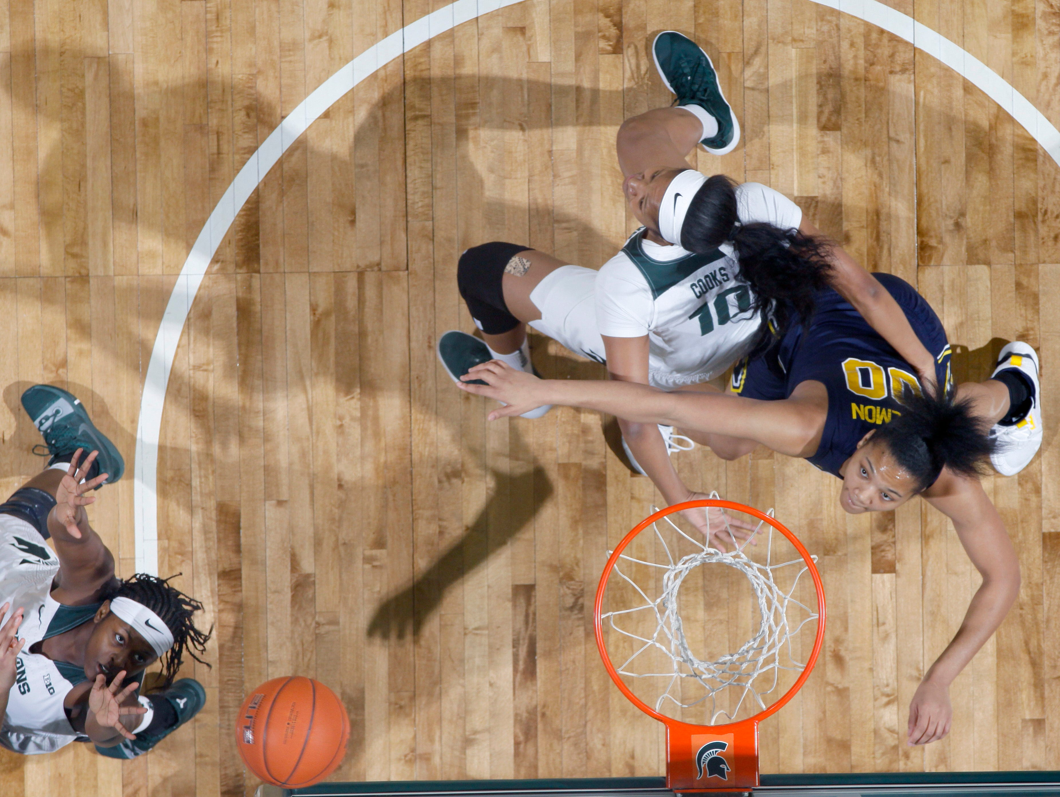 Michigan's Naz Hillmon, right, and Michigan State's Sidney Cooks, center, and Nia Hollie, left, vie for a rebound during the first quarter.