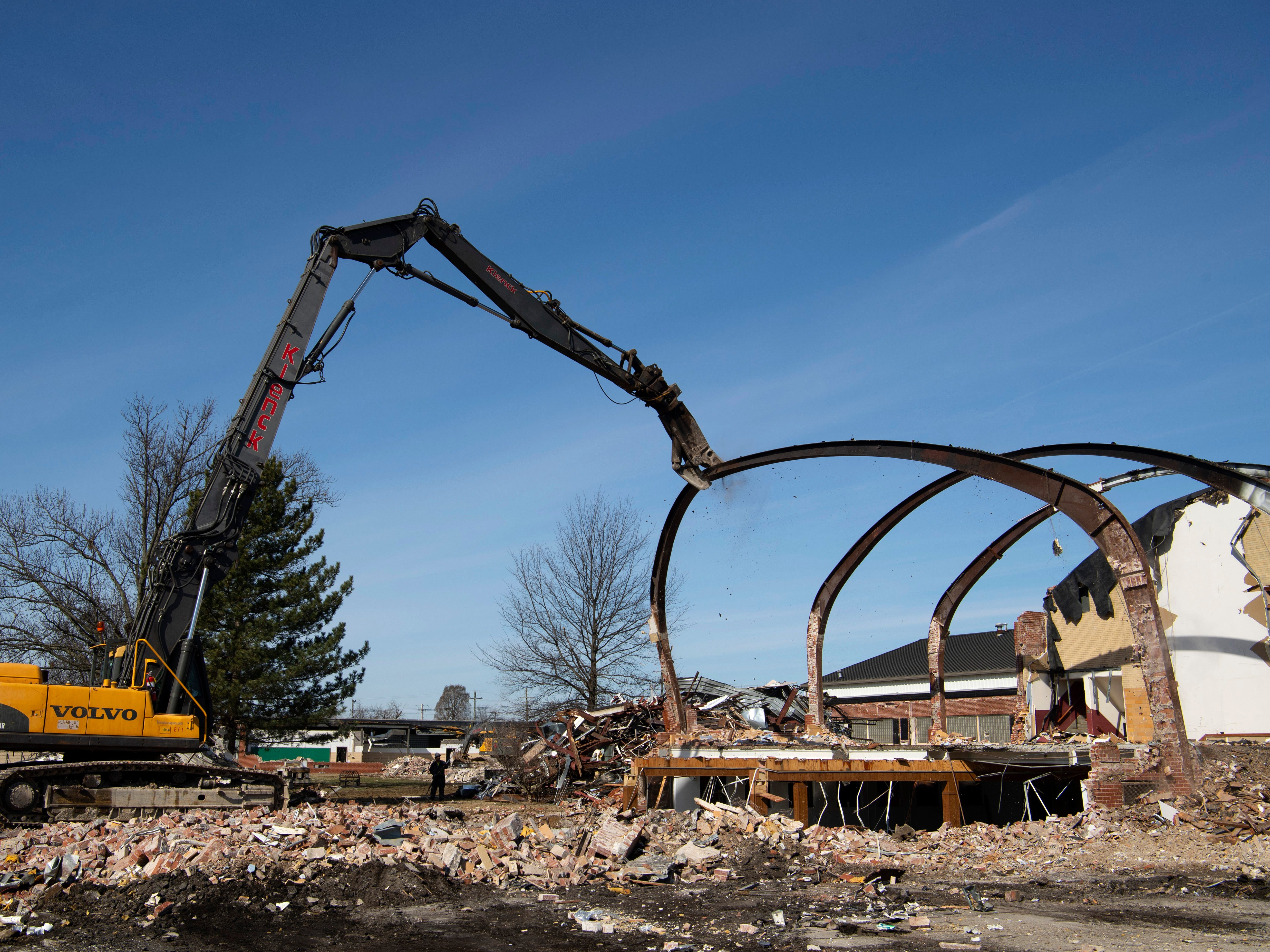 An ultra high reach excavator is used to pull down the steel beams of St. Theresa Catholic School Monday morning. Klenck Company is razing the old school methodically in order to distinguish what might be reusable or used as scrap.