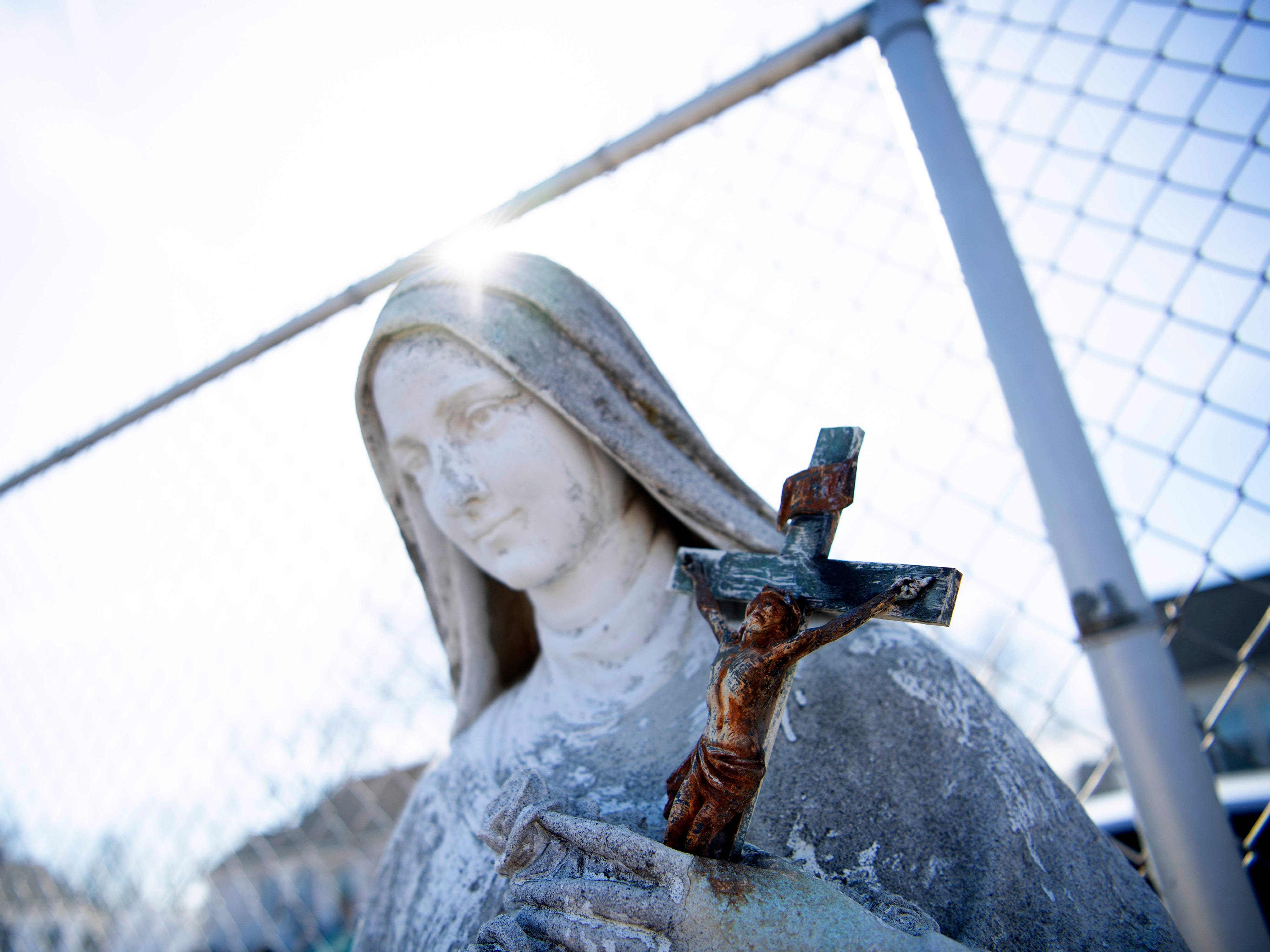 A statue of Saint Theresa holding a crucifix is tethered to a chain link fence for protection as St. Theresa Catholic School is demolished Monday morning.