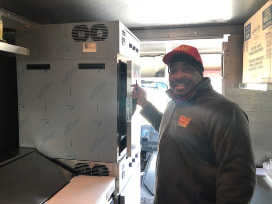 Yummy Bones Barbecue Founder Robert Meredith stands besides one of the Slow Pro oven inside the restaurant's food truck.