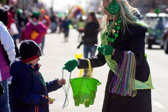 A staff member from Kitty O'Reillys Irish Pub hands out beads and candy to St. Patrick's Day Parade spectators. Entries are now being accepted for this year's parade.