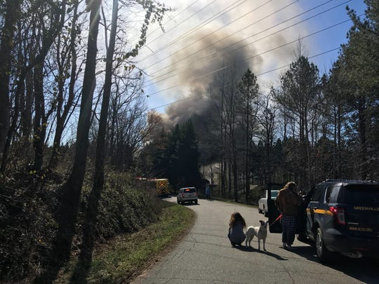 Smoke rises from a Greenville County residence where US Marshals arrested a wanted subject who barricaded himself into a home before firing gunshots. A fire broke out shortly before the suspect was arrested. February 25, 2019