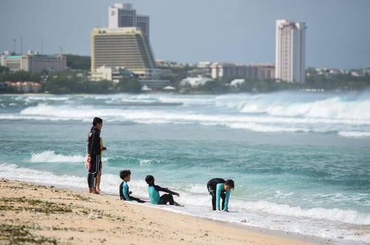 A tourist family spends time on the shore of Gun Beach in Tumon in this Feb. 25 file photo.