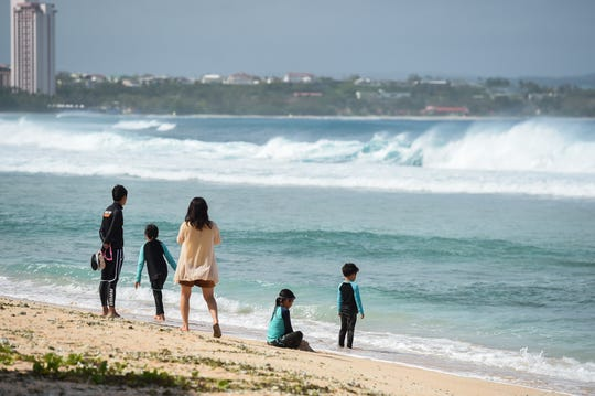 Tourists watch breaking waves at Gun Beach in Tumon in this Feb. 25 file photo.