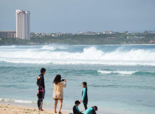 Tourists watch breaking waves at Gun Beach in Tumon, Feb. 25, 2019.