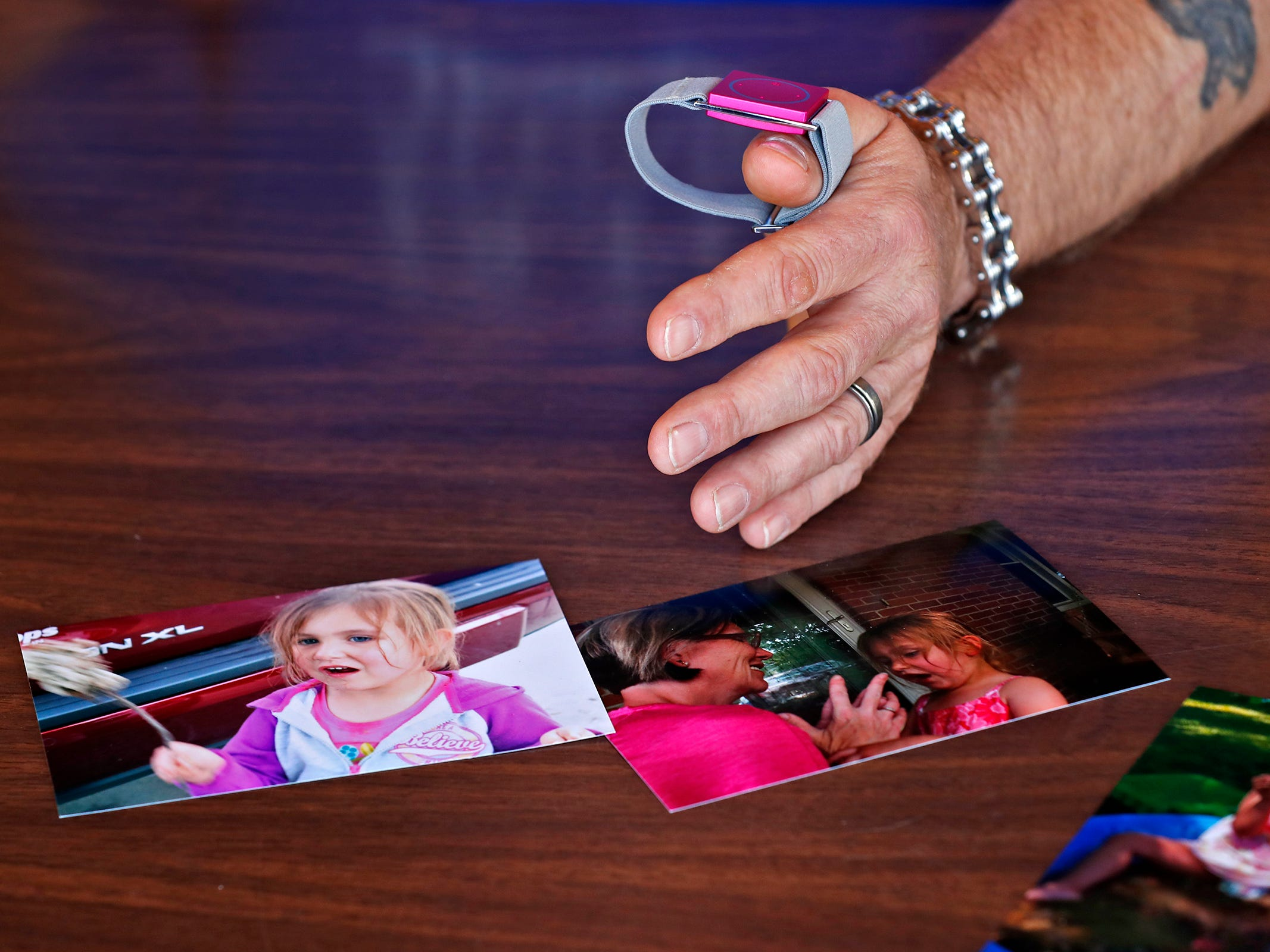 Dave Curtis holds his daughter Charly's seizure monitor, Thursday, Feb. 21, 2019. Photos of her lay in front of him.  Charly was born with a genetic condition that eventually led her to develop grand mal seizures. After trying many medications that would work at first then become ineffective, they eventually tried treating her with THC, which has been known to help children with seizures.  But in Indiana, that meant going through a lot of bureaucratic red tape.  When their THC was about to run out, Charly's father drove to Colorado to replenish their supply.  In his absence, Charly had a seizure and died.  The New Castle family wants to share their story to promote the legalization of medical marijuana.