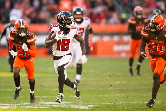 Nov 11, 2018; Cleveland, OH, USA; Atlanta Falcons wide receiver Calvin Ridley (18) runs the ball for a first down as Cleveland Browns cornerbacks Denzel Ward (21) and Briean Boddy-Calhoun (20) chase him during the fourth quarter at FirstEnergy Stadium.