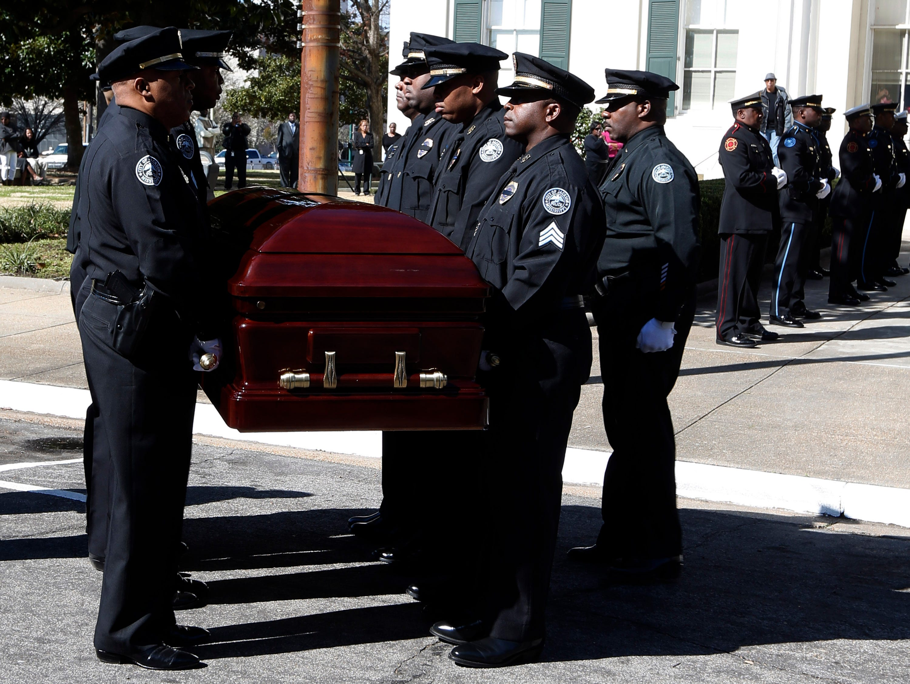 Jackson Police Department honor guard carry the casket bearing the body of the late Mayor Chokwe Lumumba into City Hall past a combined Fire and Police Departments honor guard, Friday, March 7, 2014 in Jackson, Miss. Lumumba, who will lie in state Friday, died Feb. 25.