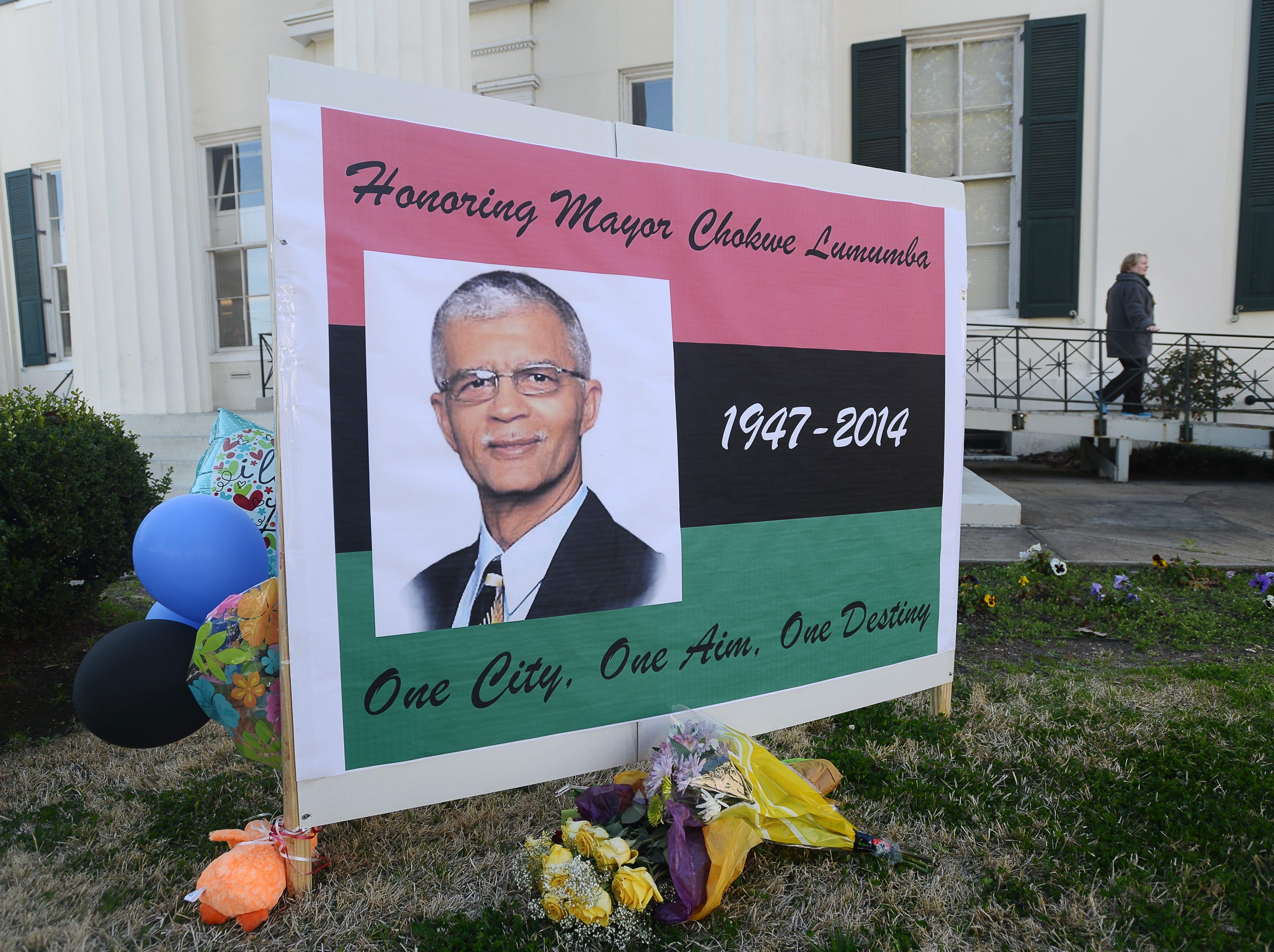 A sign, adorned with balloons and flowers, stands outside City Hall in memorial to Mayor Chokwe Lumumba.