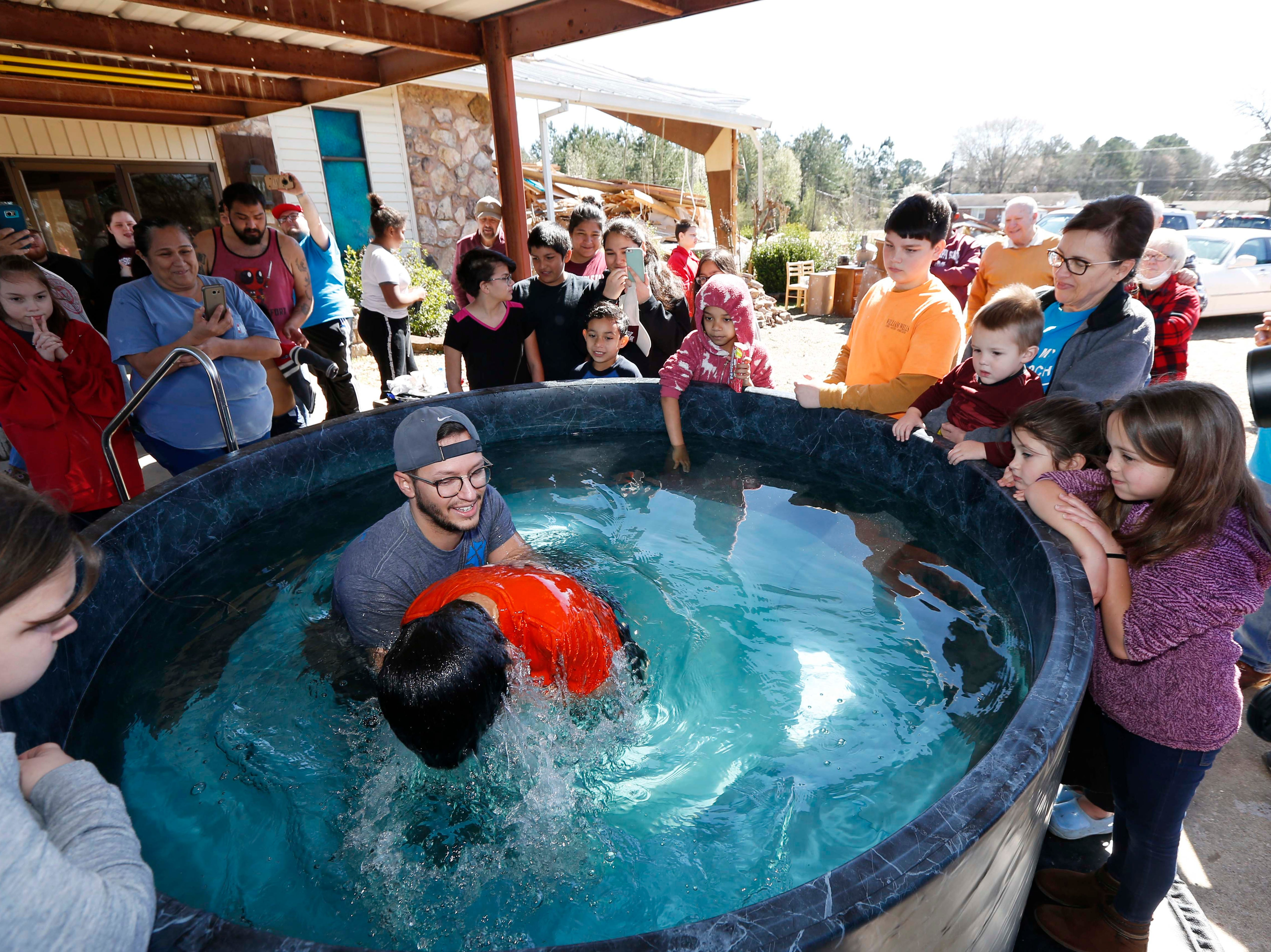 Church members watch as student pastor Craig Blaylock, left, baptizes a church member at the First Pentecostal Church in Columbus, Miss., Sunday morning, Feb. 24, 2019. The church, in the background, was destroyed by a tornado Saturday afternoon, but church members opted to go ahead with the baptisms as planned. (AP Photo/Rogelio V. Solis)