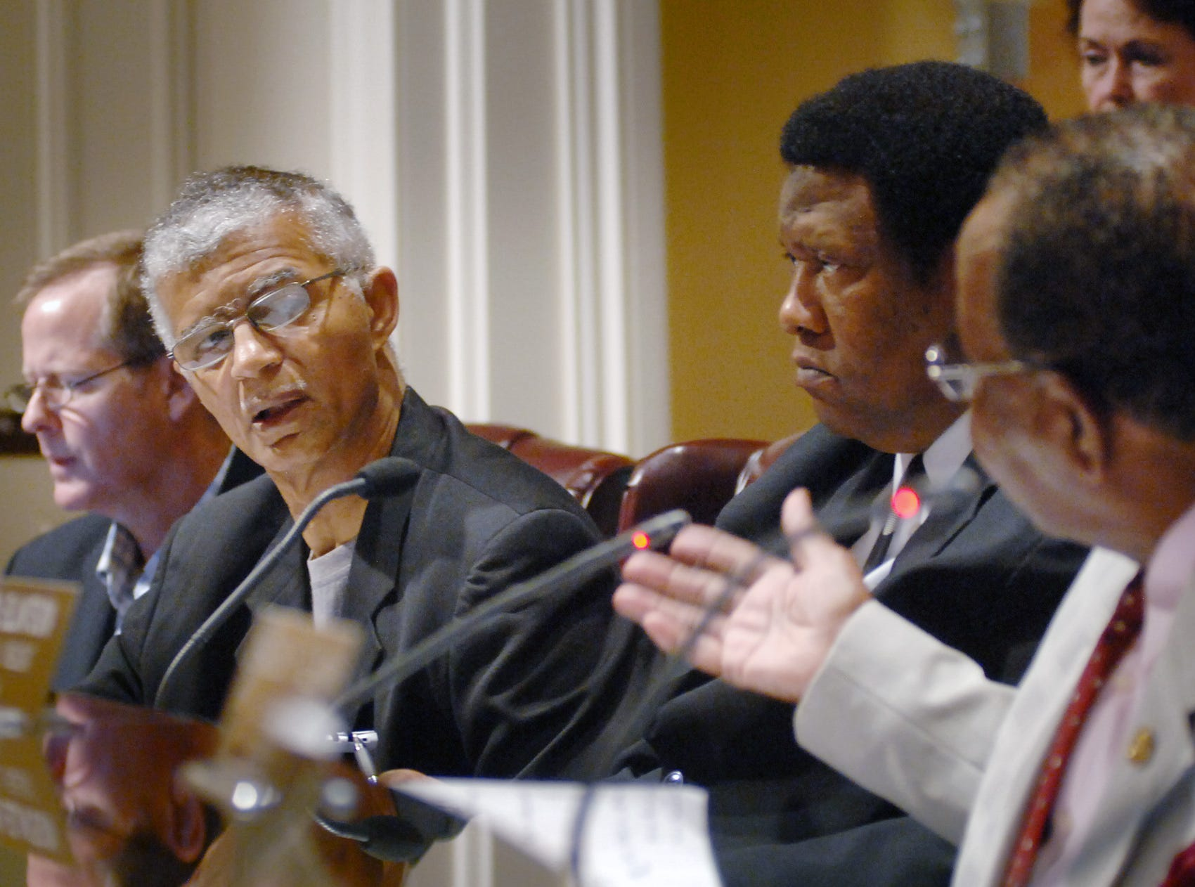 Jackson City Councilman Chokwe Lumumba (second from left) listens to council President Frank Bluntson (right) during Tuesday's council meeting at City Hall.  During the meeting, the two repeatedly sparred over the amount of public comment to entertain during the regular meeting on the issue of an ordinance to ban profiling. Later in the meeting, the council decided to schedule a public forum for Thursday, August, 19.
