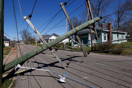 Downed telephone poles on 15th Street in Columbus, Miss., Sunday, Feb. 24, 2019, following Saturday's tornado. (AP Photo/Rogelio V. Solis)