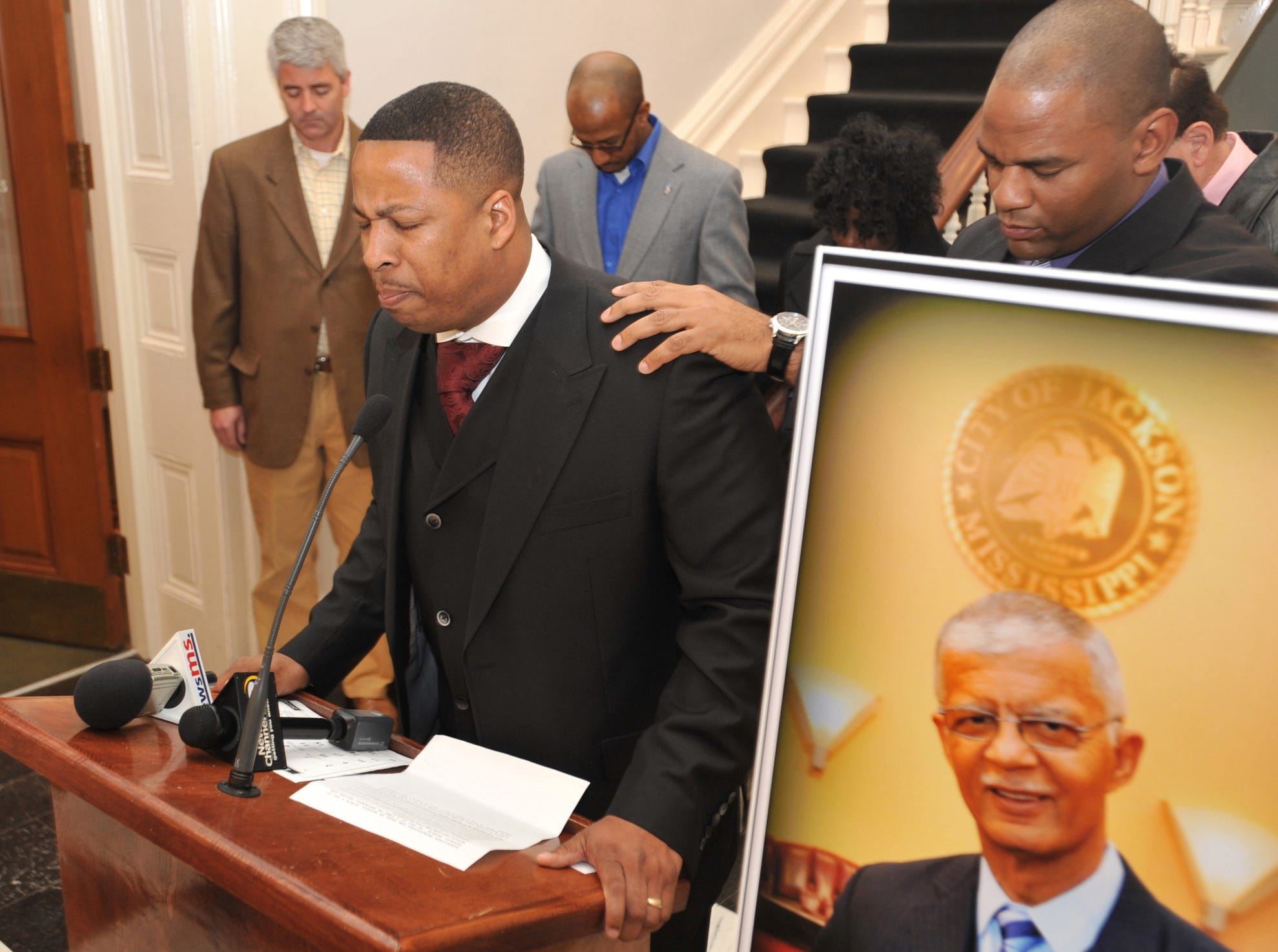 The Rev. Roderick Richardson, left, of The Word Center in Jackson, and Jackson Ward 4 City Councilman De'Keither Stamps lead prayers near a portrait of the late Jackson Mayor Chokwe Lumumba Tuesday at City Hall. Jackson City Council members declared the next seven days a period of prayer, mourning and reflection on the accomplishments of Lumumba.