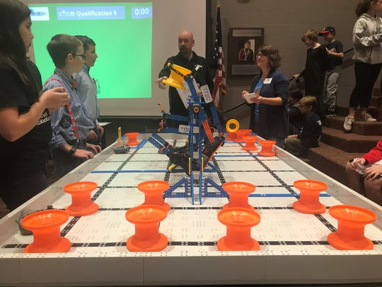 The robotics teams compete by moving orange and yellow cones on the table to a designated corner to score points and achieve other feats with their robots including hanging on bars in the middle of the table.