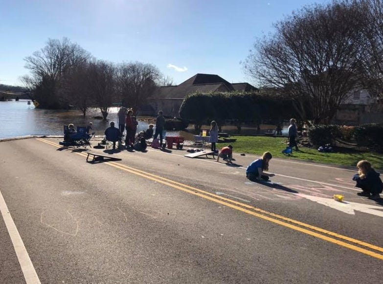 Northshore Hills subdivision residents hold a tailgate in the middle of Northshore Dr. on Sunday, Feb. 24, 2019. Water blocked both entrances to the subdivision since heavy flooding began Saturday.