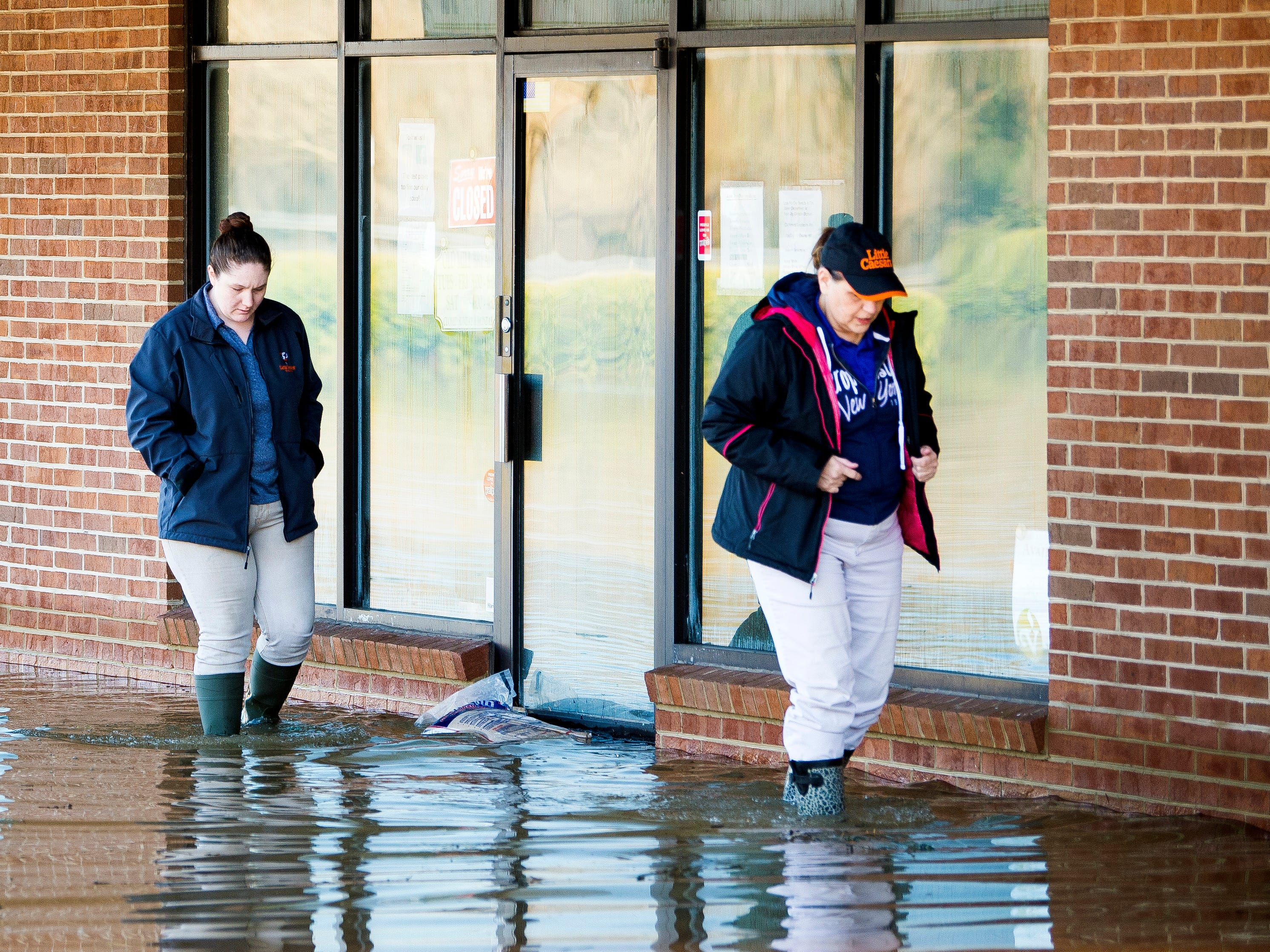 Little Caesars employees walk through floodwaters after checking in on the Little Caesars store in the North Cedar Bluff Plaza on N. Cedar Bluff Road on Monday, February 25, 2019.