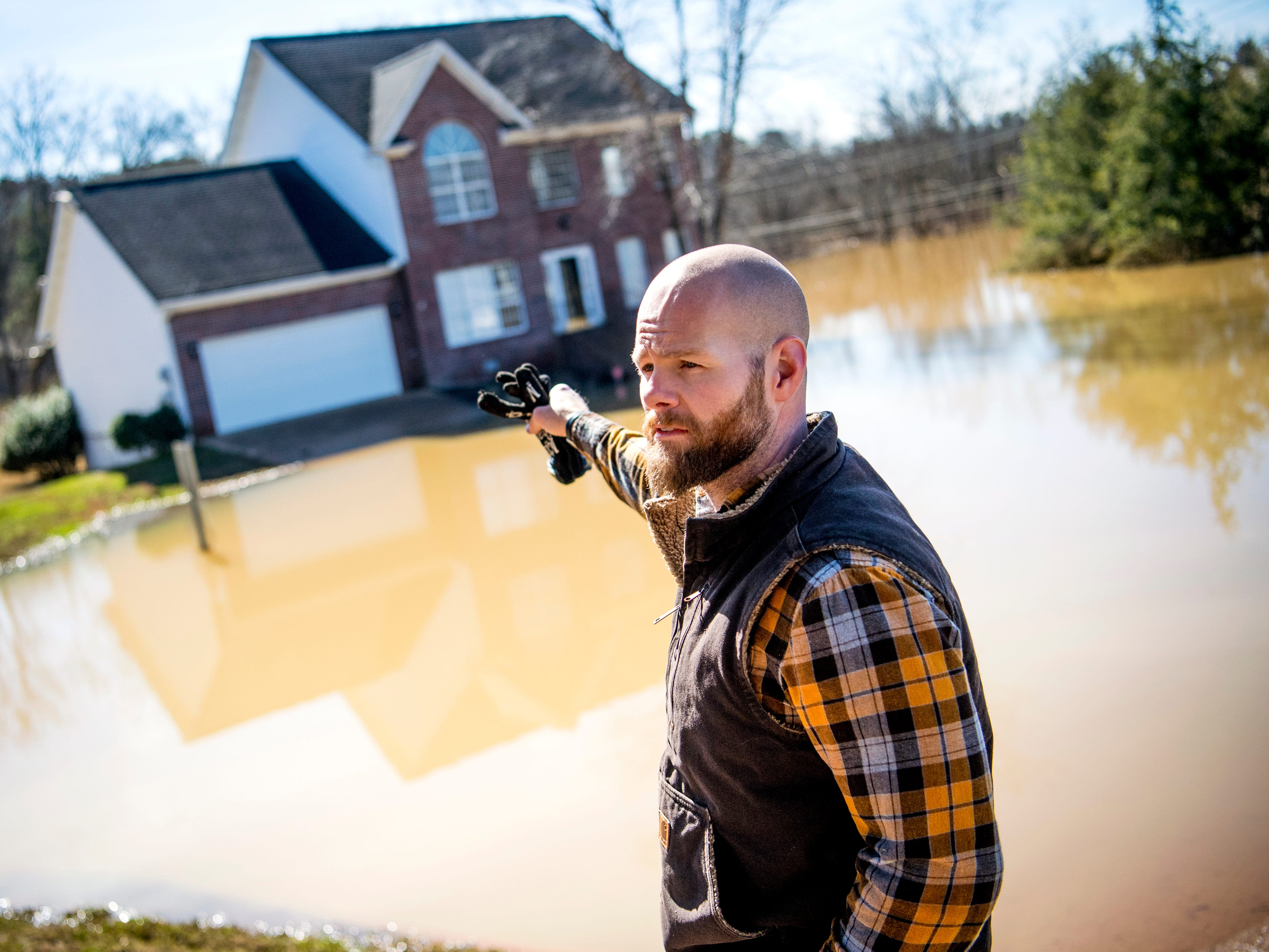 Jeff Macklin points back at expansive flooding on Ebenezer Road near the Lennox Place subdivision in Knoxville on Monday, February 25, 2019. Macklin's basement flooded with seven feet of water on Saturday, and the water is now at about three feet deep in his basement as of Monday.