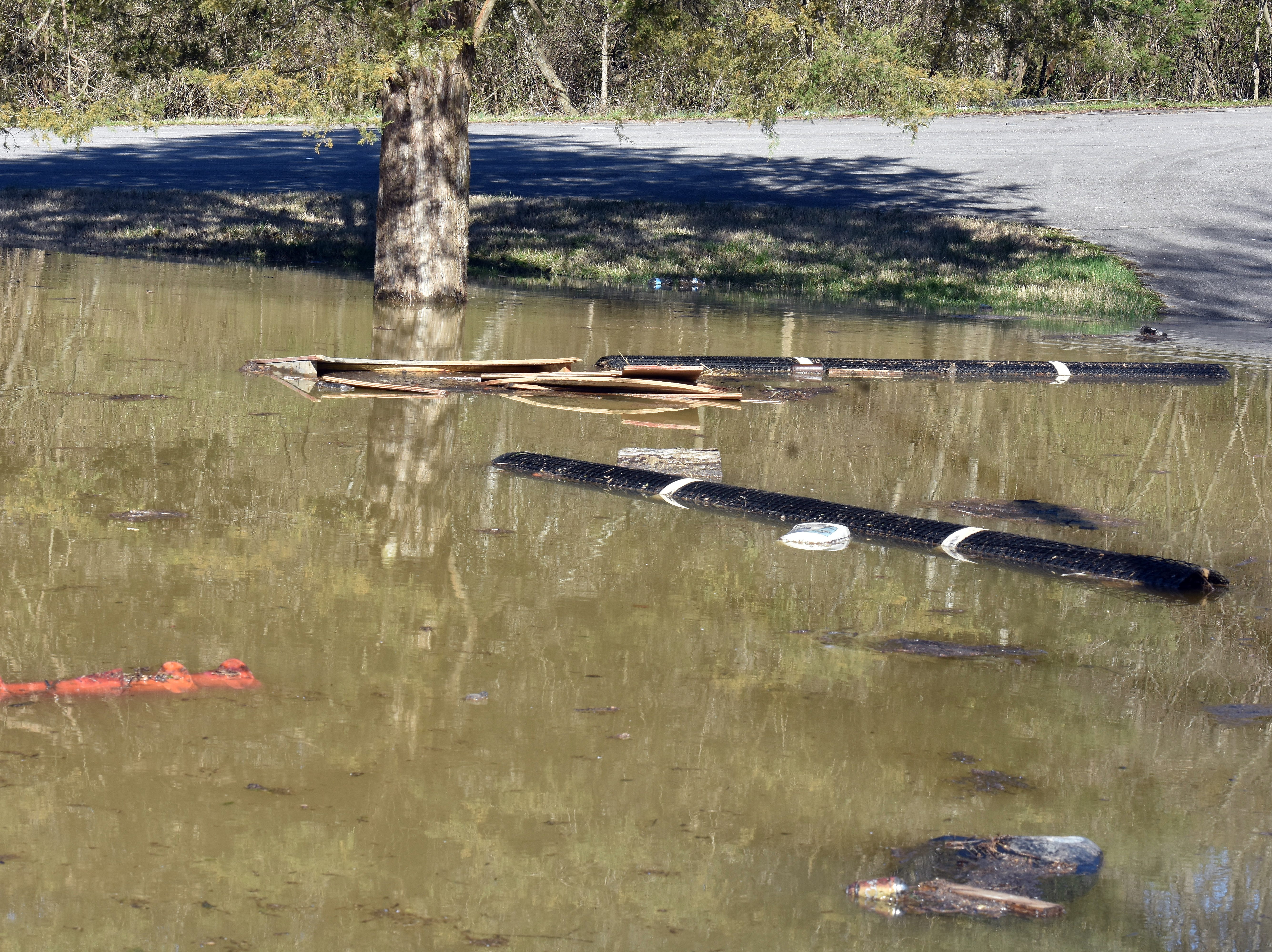 Debris floats in flood waters in the side lot of Harrison Construction Company on Spring Hill Road.