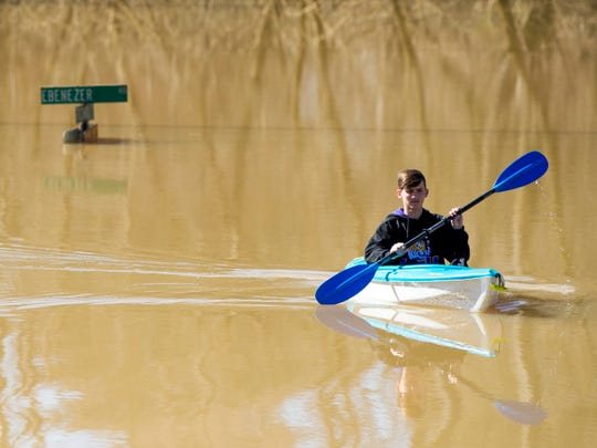 Caleb Bourque kayaks through a flooded Ebenezer Road near the Lennox Place subdivision in Knoxville on Monday, February 25, 2019.