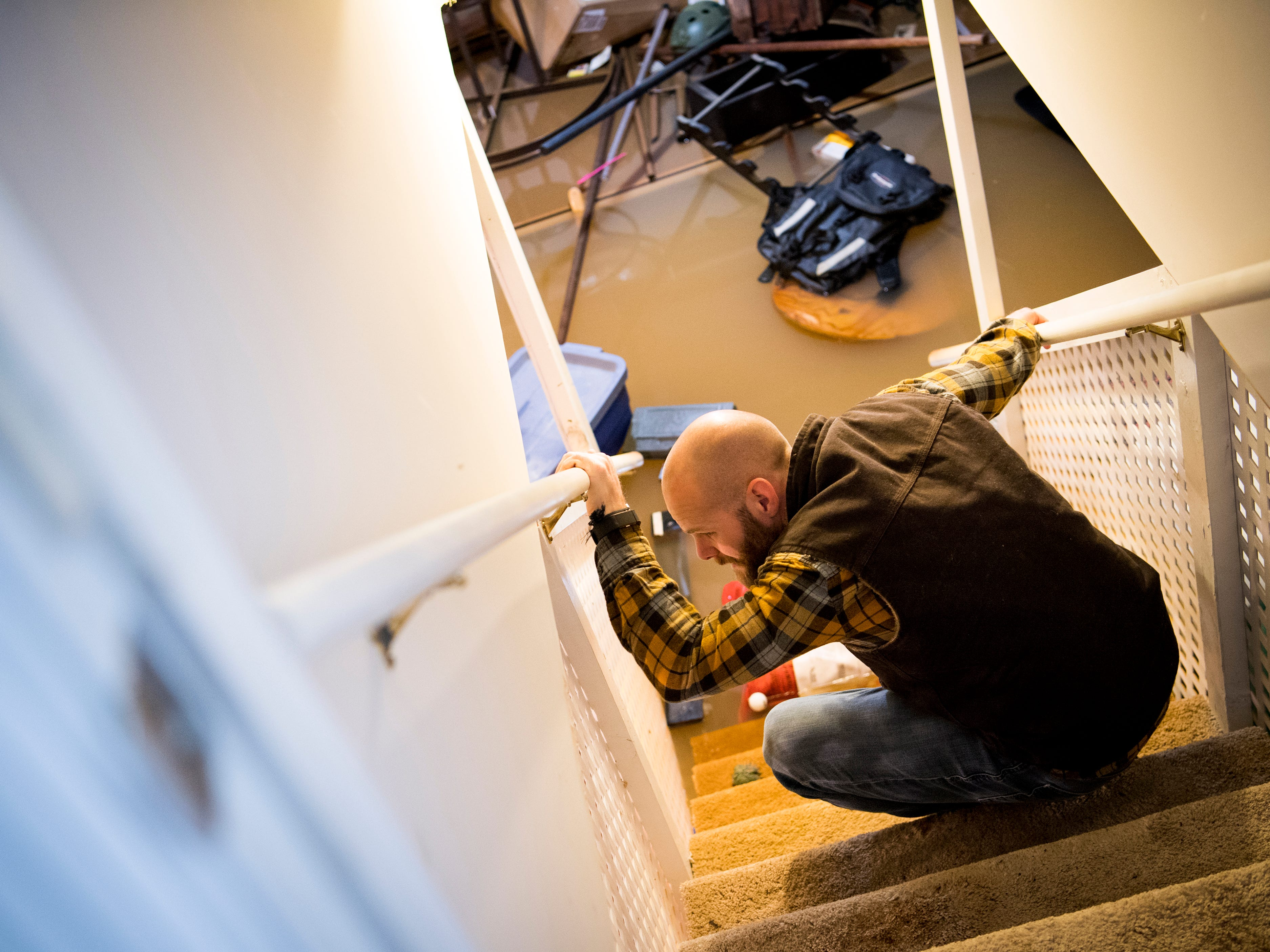 Jeff Macklin crouches down to look at his flooded basement on Monday, February 25, 2019. Macklin lives in the Lennox Place subdivision off of Ebenezer Road in Knoxville, and parts of Ebenezer Road were still under several feet of water on Monday afternoon.