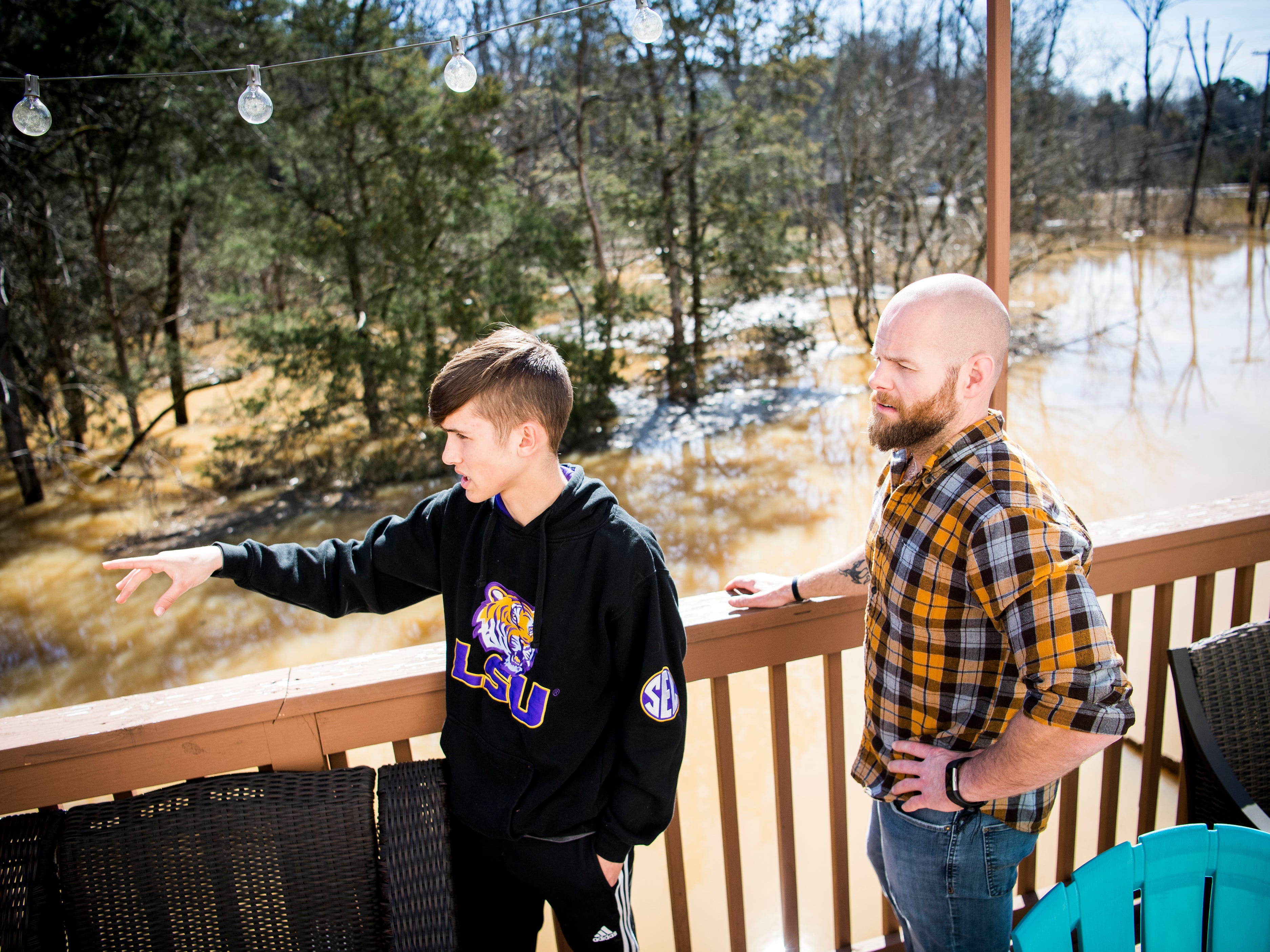 Caleb Bourque, left, and Jeff Macklin point out how high water had gotten in their backyard from their back deck on Monday, February 25, 2019. Bourque and Macklin live in the Lennox Place subdivision off of Ebenezer Road in Knoxville, and parts of Ebenezer Road were still under several feet of water on Monday afternoon.