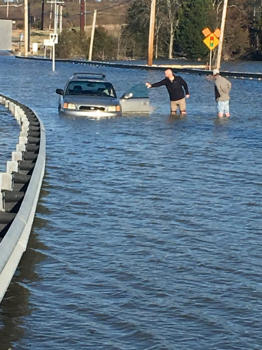 Chris Donsbach, left, helps a man out of his car on Northshore Drive Sunday.