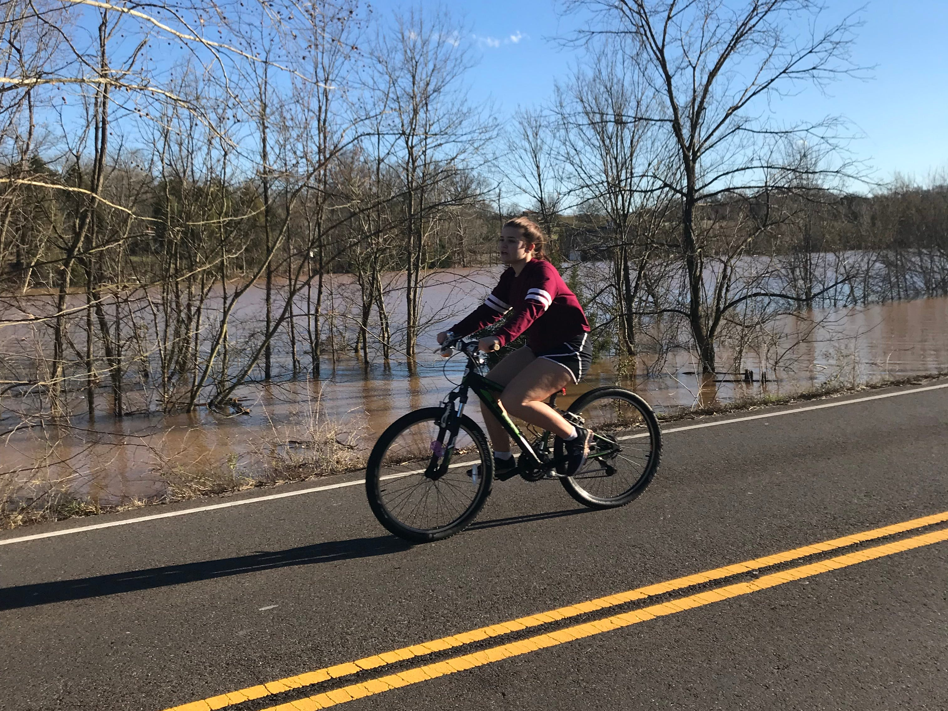 A young person bicycles down the middle of a dry stretch of Northshore Drive between the flooded areas at Ebenezer Road and Whittington Creek.
