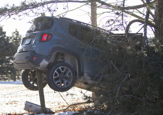 A Jeep is stuck on a fence post, with its front end having hit a tree on the east side of Rickett Road south of Maltby Road in Green Oak Township Monday, Feb. 25, 2019.