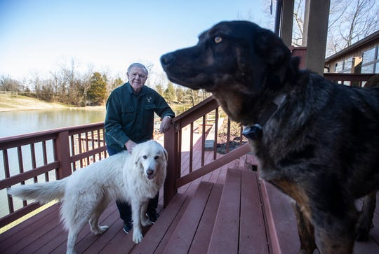 Denny Crum stands on the deck of his home with two of his dogs – Itty Bitty, left, and Zeke, right.