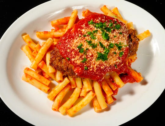 Silvio's Chicken Parmesan is served with marinara sauce atop a fresh bed of pasta.