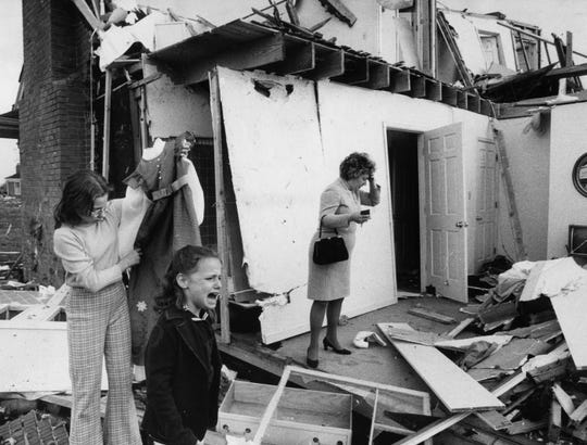Mrs. Barbara Jaggers stands stunned in the remains of her family's home on Stannye Drive in northwestern Jefferson  County while her younger daughters, Leigh Ann, 7, cries in disbelief. April 3, 1974