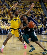 Michigan State guard Cassius Winston (5) drives on Michigan guard Zavier Simpson (3) during the second half of an NCAA college basketball game, Sunday, Feb. 24, 2019, in Ann Arbor, Mich.