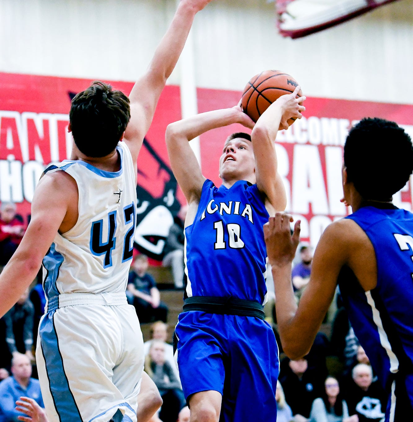 Ionia's Nick Szymanski, right, makes a basket and is fouled as Lansing Catholic's Charlie Nylander, left, defends during a Division 2 district opener in February. The MHSAA Representative Council approved seeding at he district level of the state tournament for next school year.