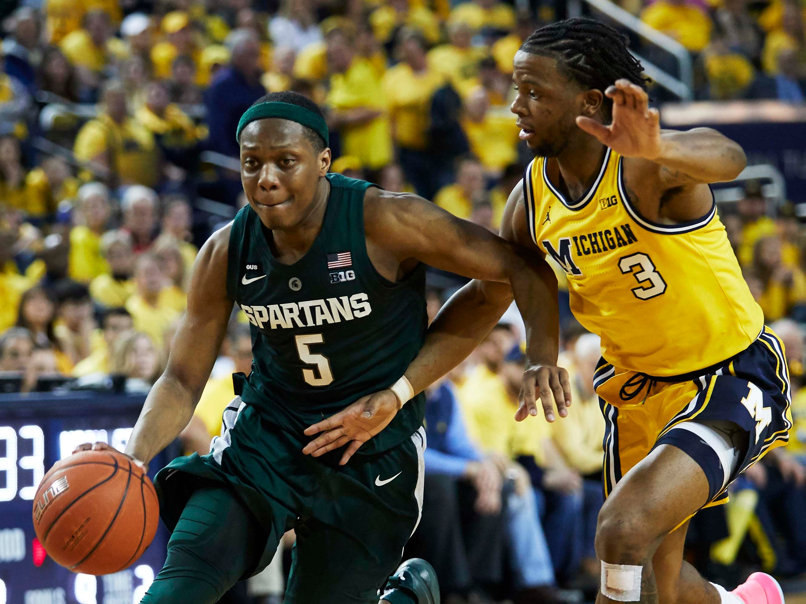 Michigan State Spartans guard Cassius Winston (5) dribbles defended by Michigan Wolverines guard Zavier Simpson (3) in the second half at Crisler Center.
